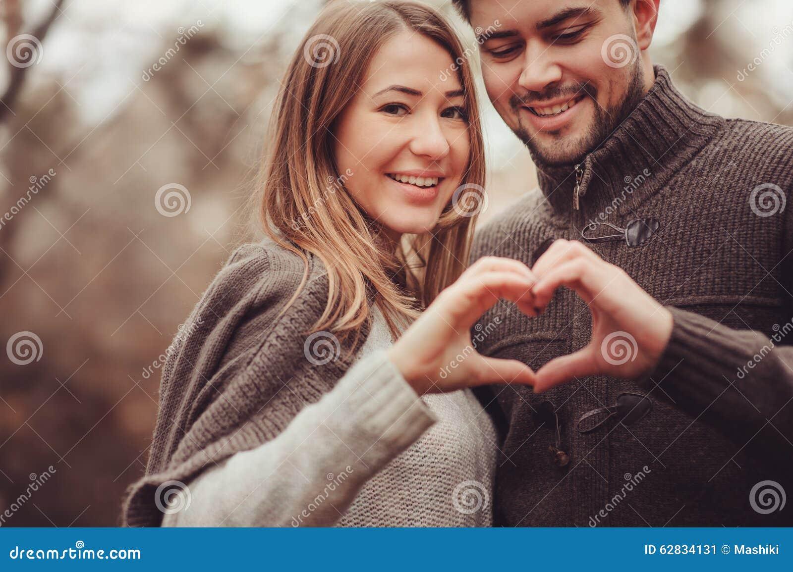 显示心脏的年轻愉快的爱恋的夫妇为在舒适室外步行的情人节在森林
