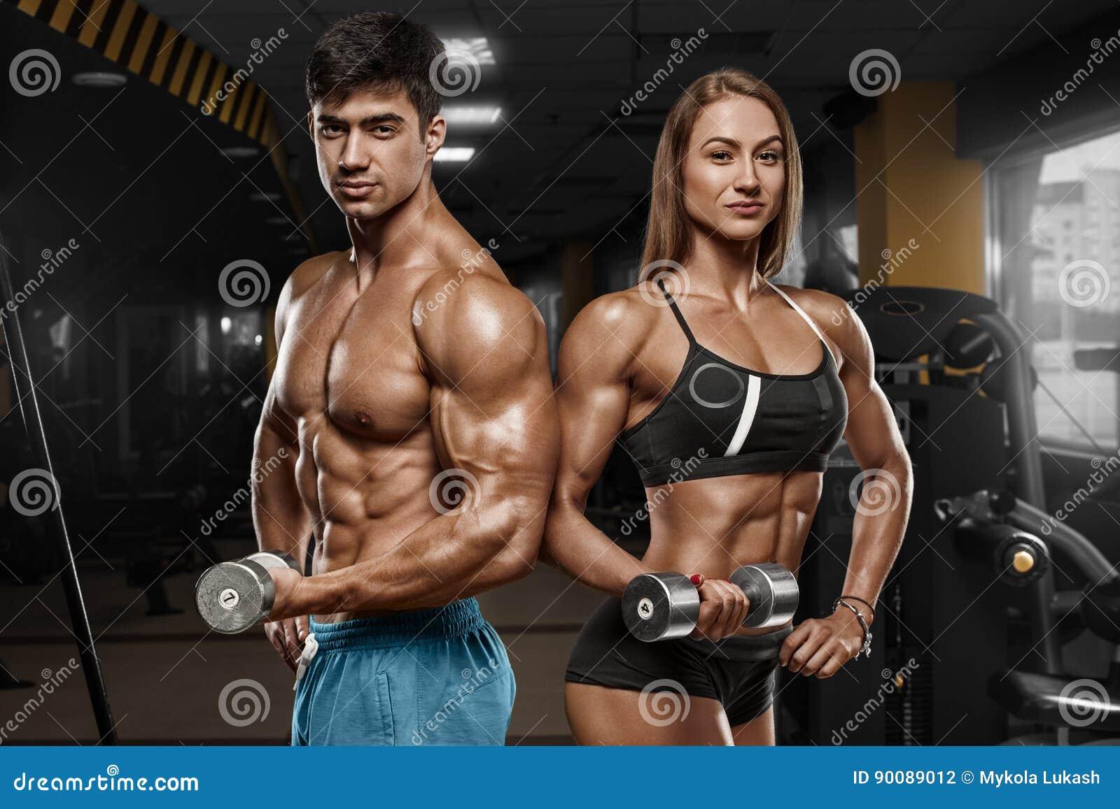 显示肌肉和锻炼的运动的性感的夫妇在健身房 肌肉人和wowan