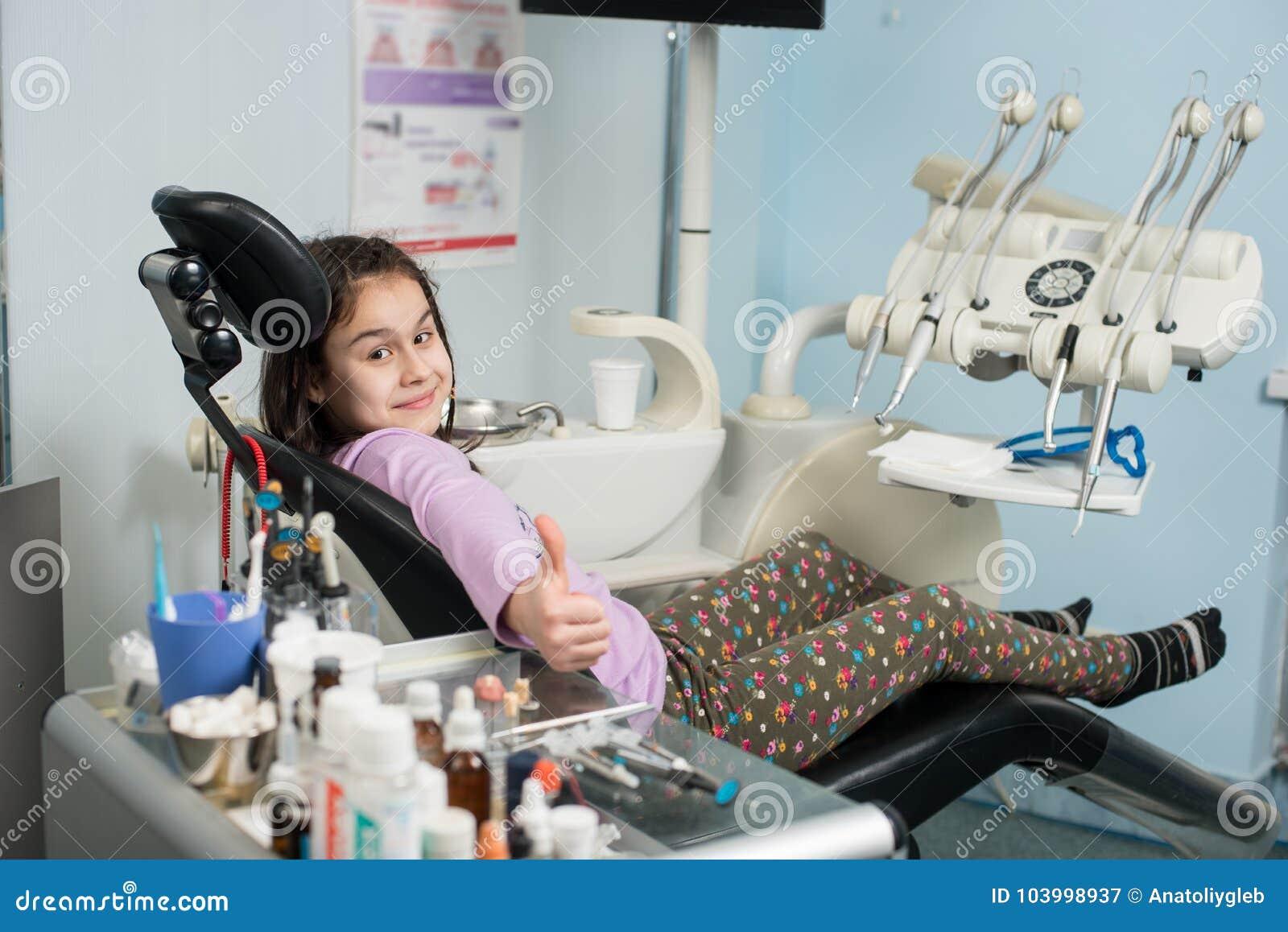 显示赞许的愉快的耐心女孩在牙齿诊所办公室 医学、口腔医学和医疗保健概念