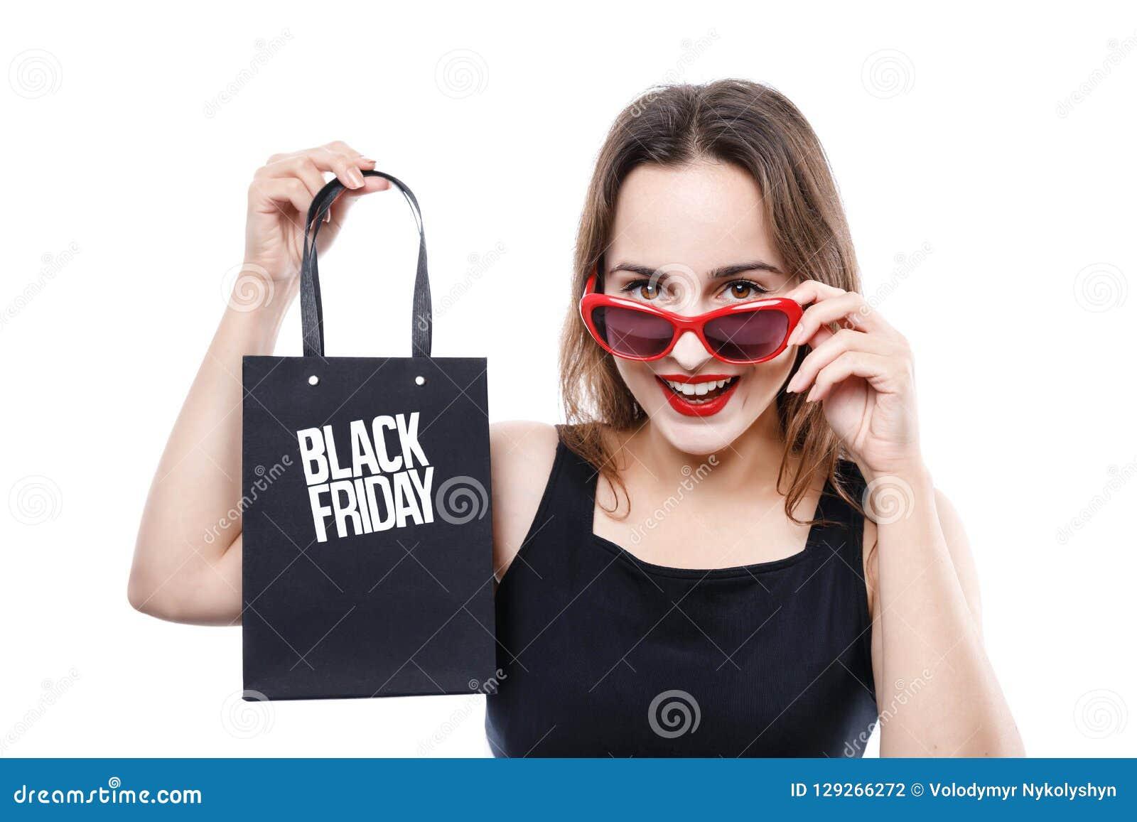 显示黑星期五购物袋的时髦的逗人喜爱的女孩