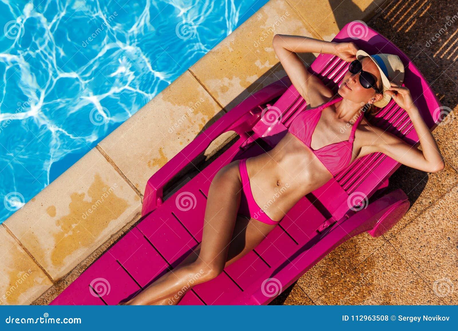 晒日光浴在太阳床上的性感的妇女由游泳池