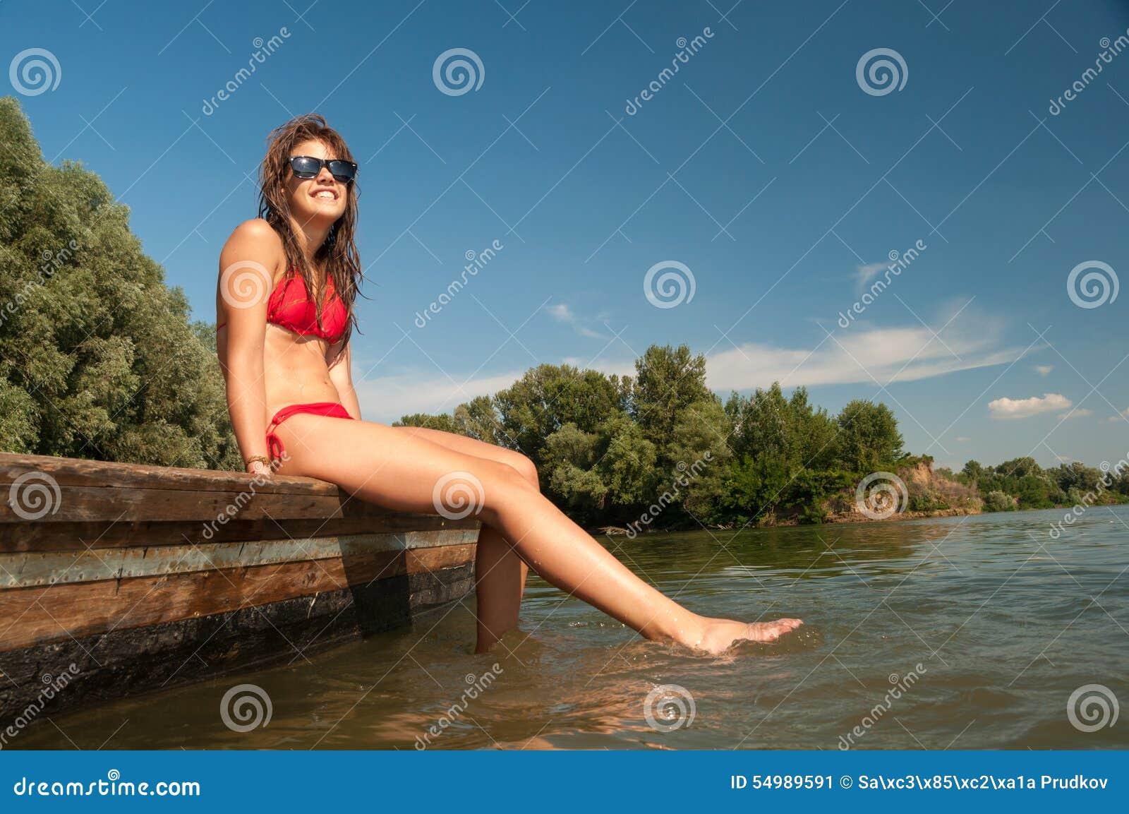 晒日光浴在河船的相当微笑的十几岁的女孩