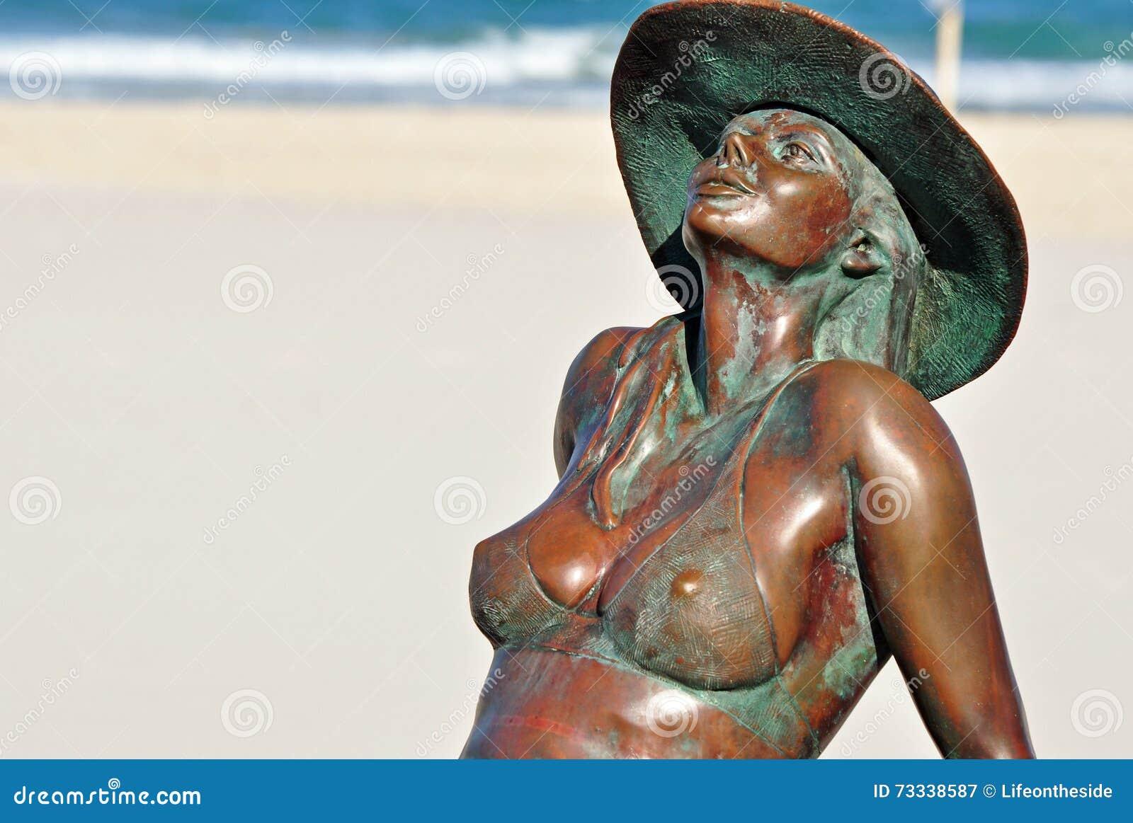 晒日光浴在海滩英属黄金海岸的被镀青铜的美丽的比基尼泳装女孩