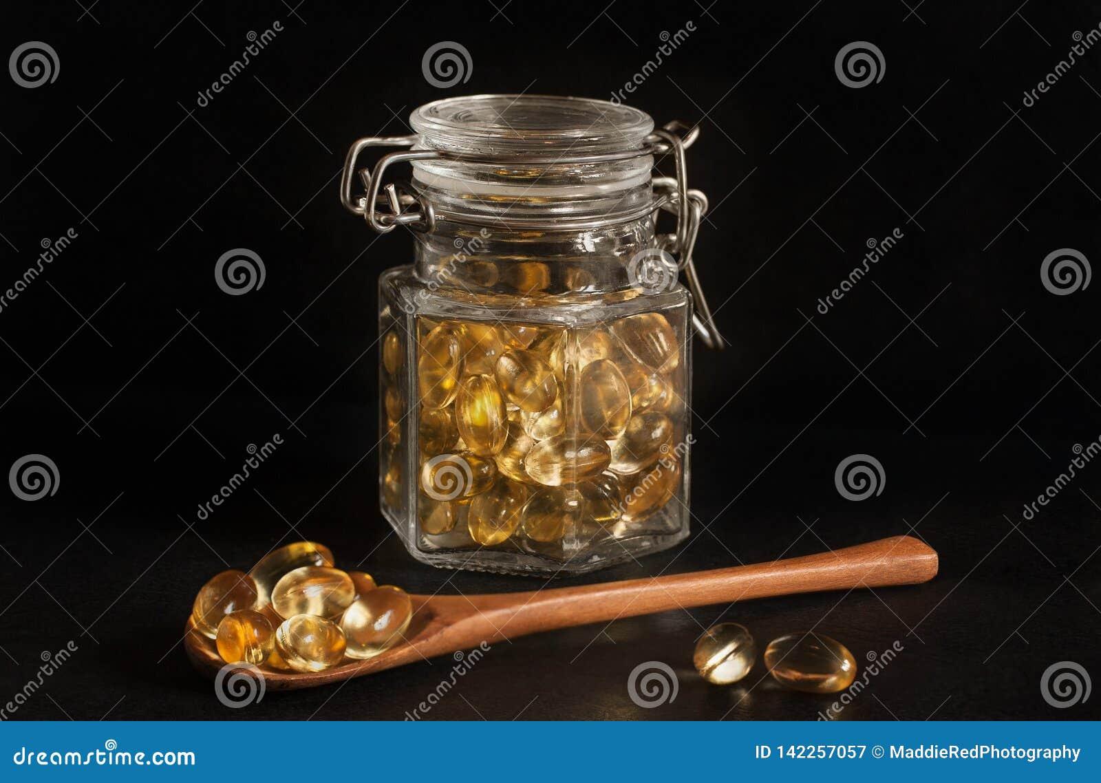 晚樱草胶囊在一个玻璃瓶子和在一把木匙子