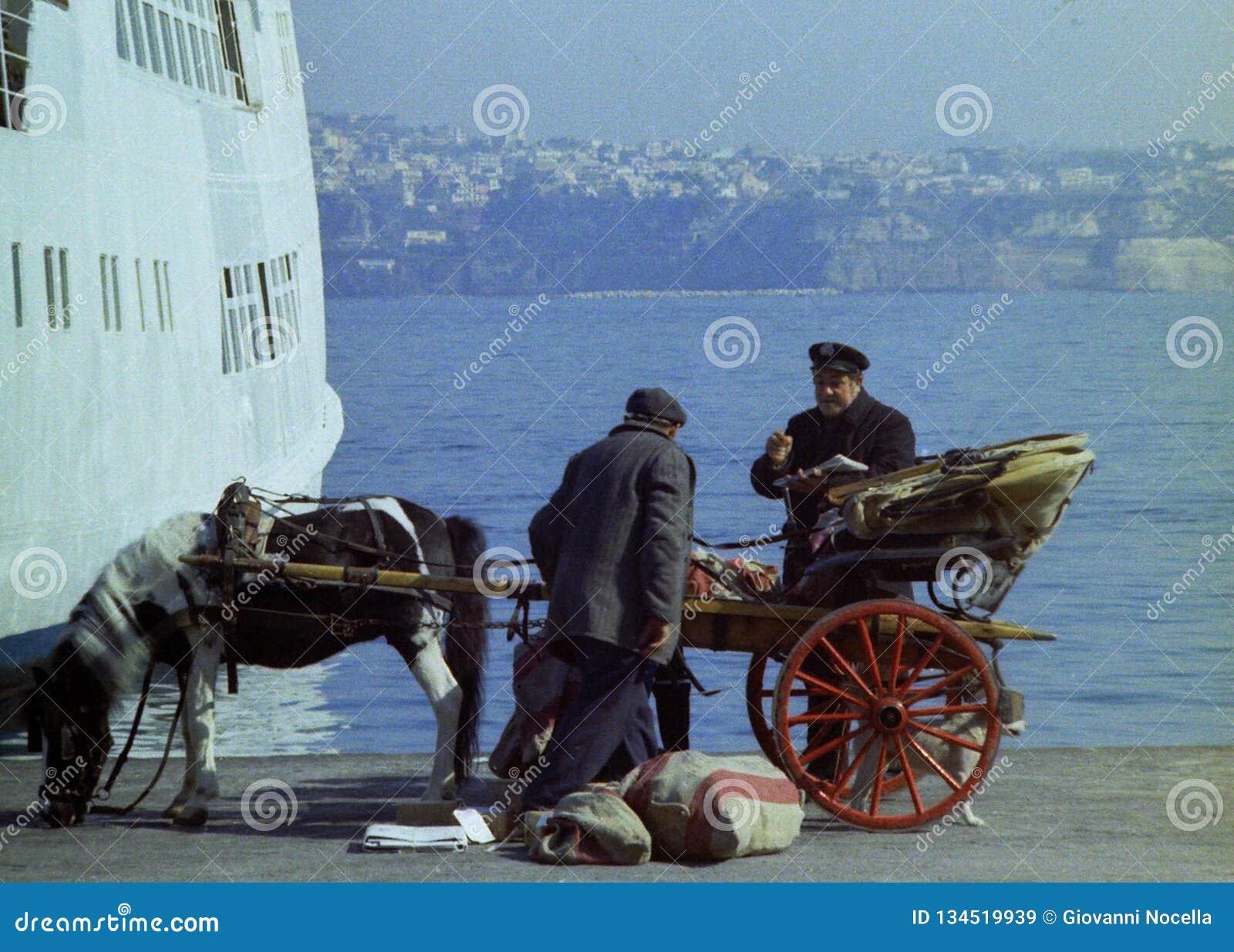 普罗奇达,意大利,1974年-有推车和马的意大利邮差与在普罗奇达码头的邮政大袋