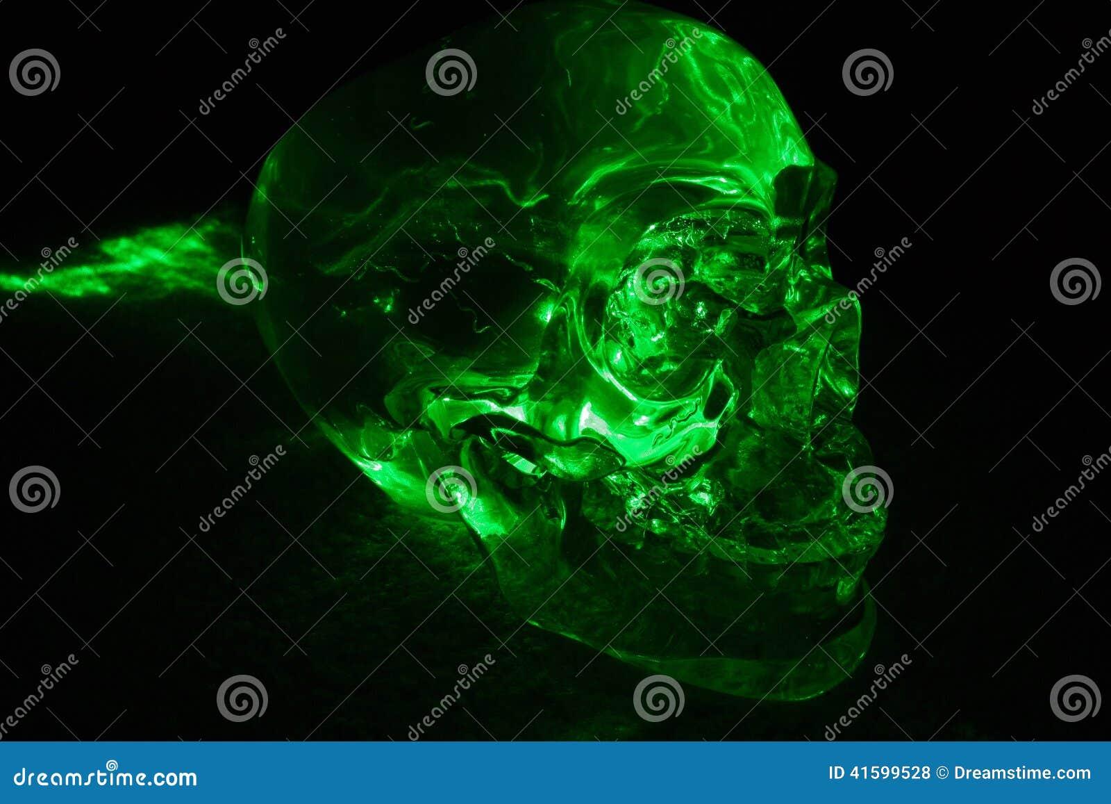 有绿色激光焕发的水晶头骨在石英.