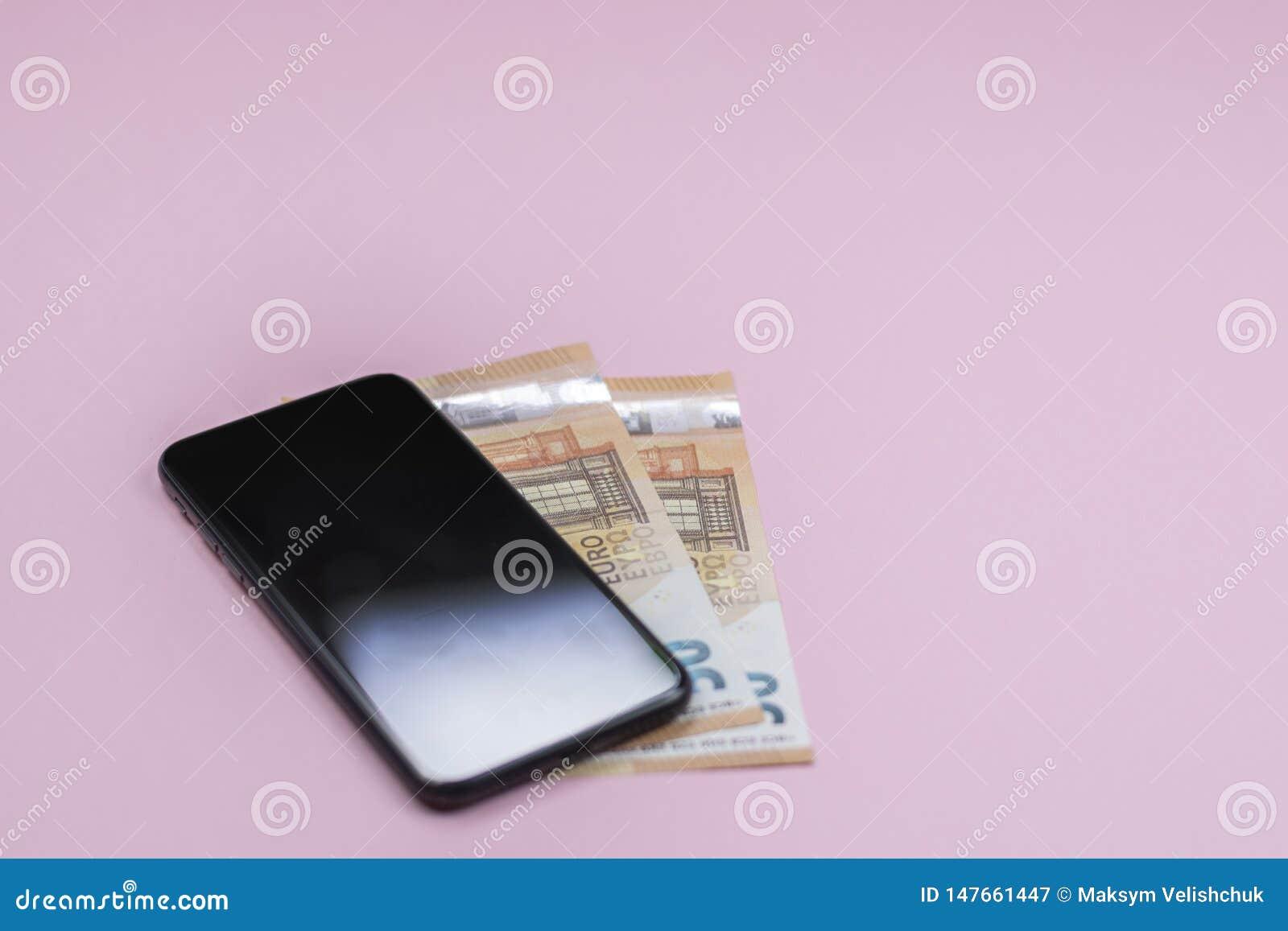 智能手机特写镜头有金钱的在桃红色背景