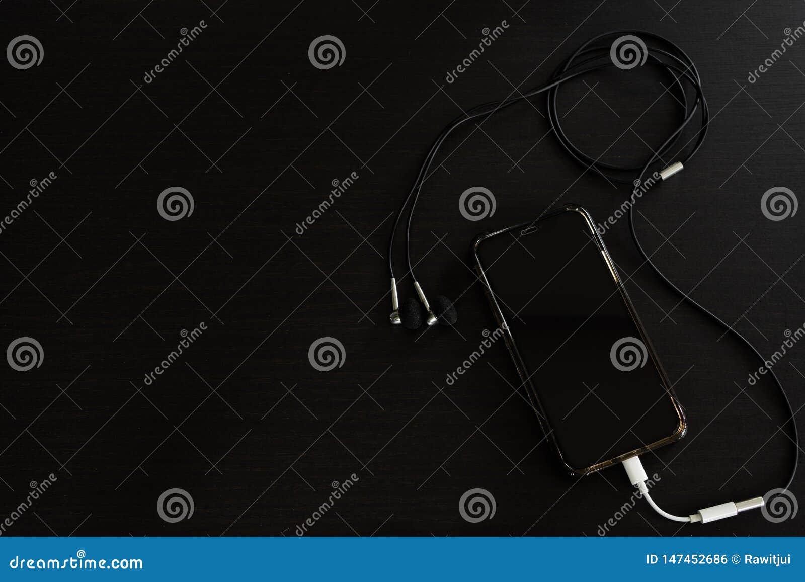 智能手机,与耳机的iPhone x,在黑木桌上