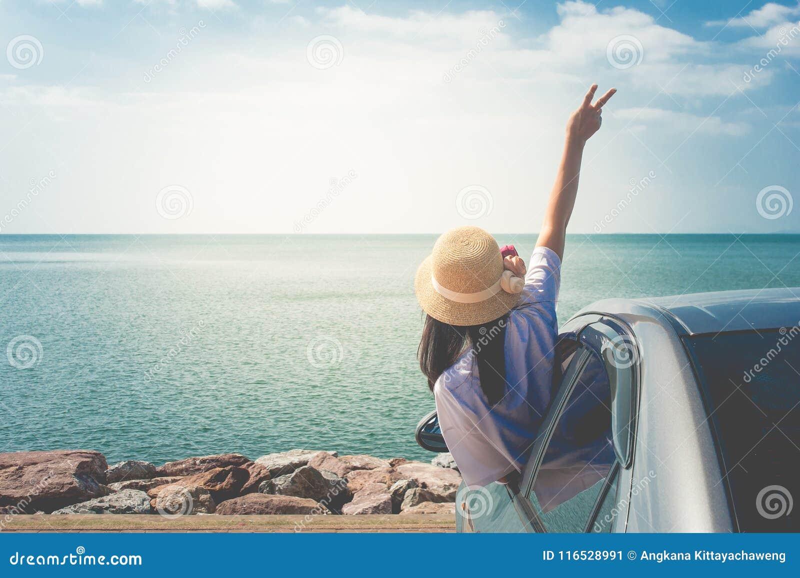 暑假和假日概念:在海的愉快的家用汽车旅行,画象妇女感觉幸福