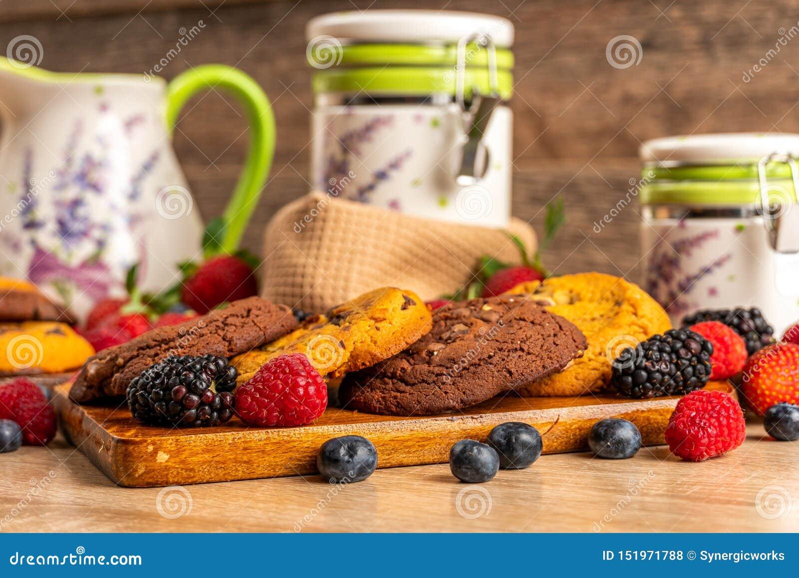 曲奇饼、莓和黑莓在木板