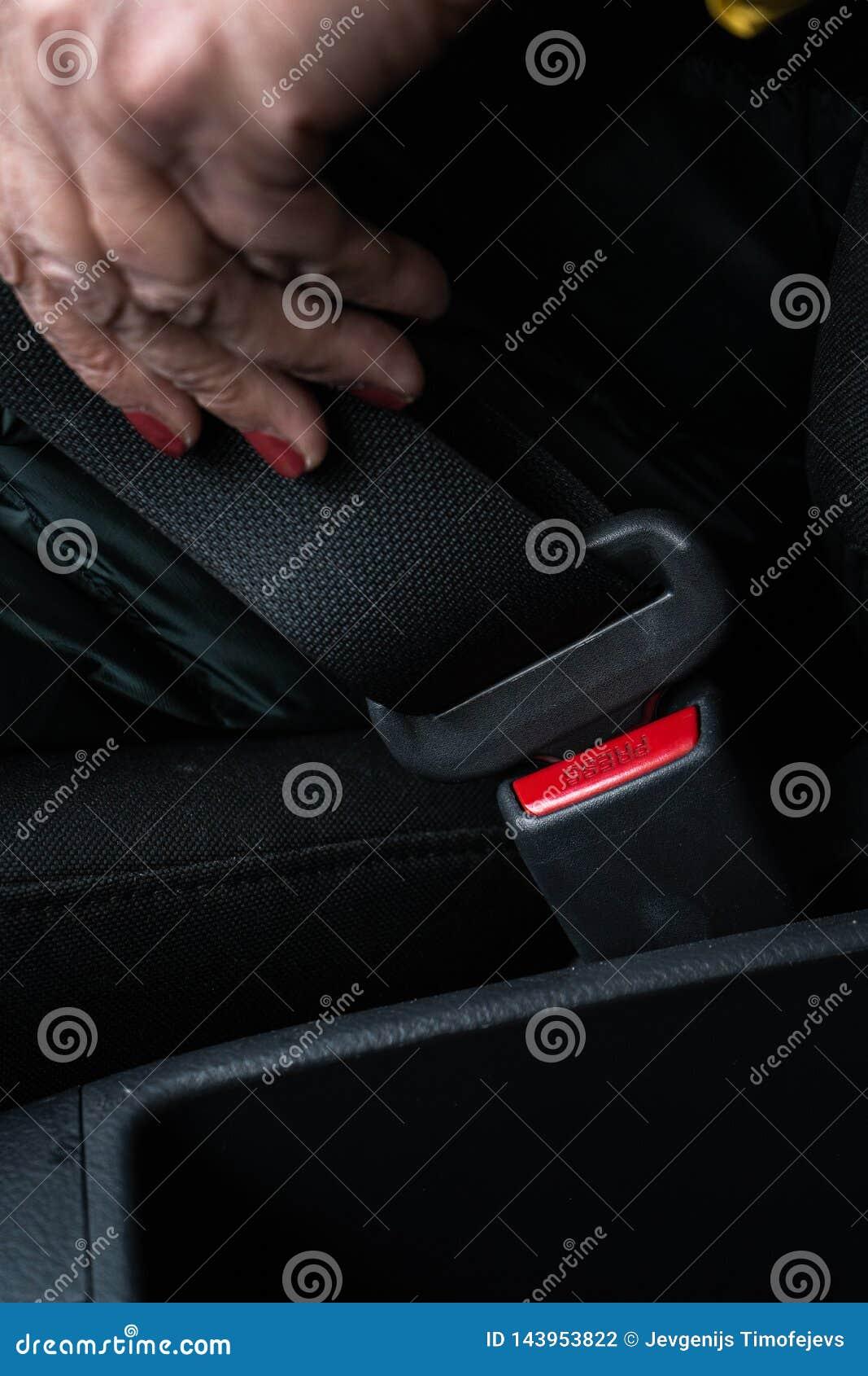 更老的资深妇女紧固在穿绿色和救生服的汽车的一个安全带