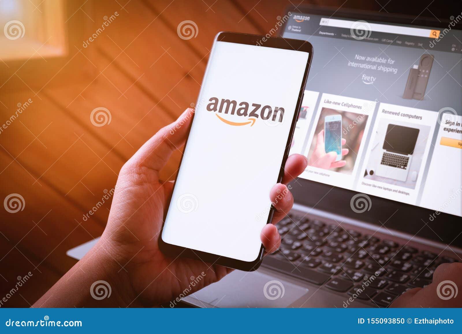 曼谷,泰国- 2019年8月5日:拿着有亚马逊商标的妇女手智能手机在屏幕和亚马逊网站上膝上型计算机的