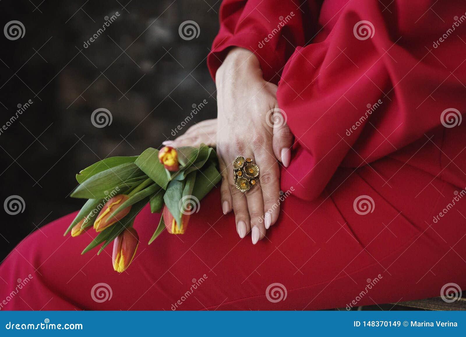 有一个圆环的女孩的手在他的手指和举行郁金香