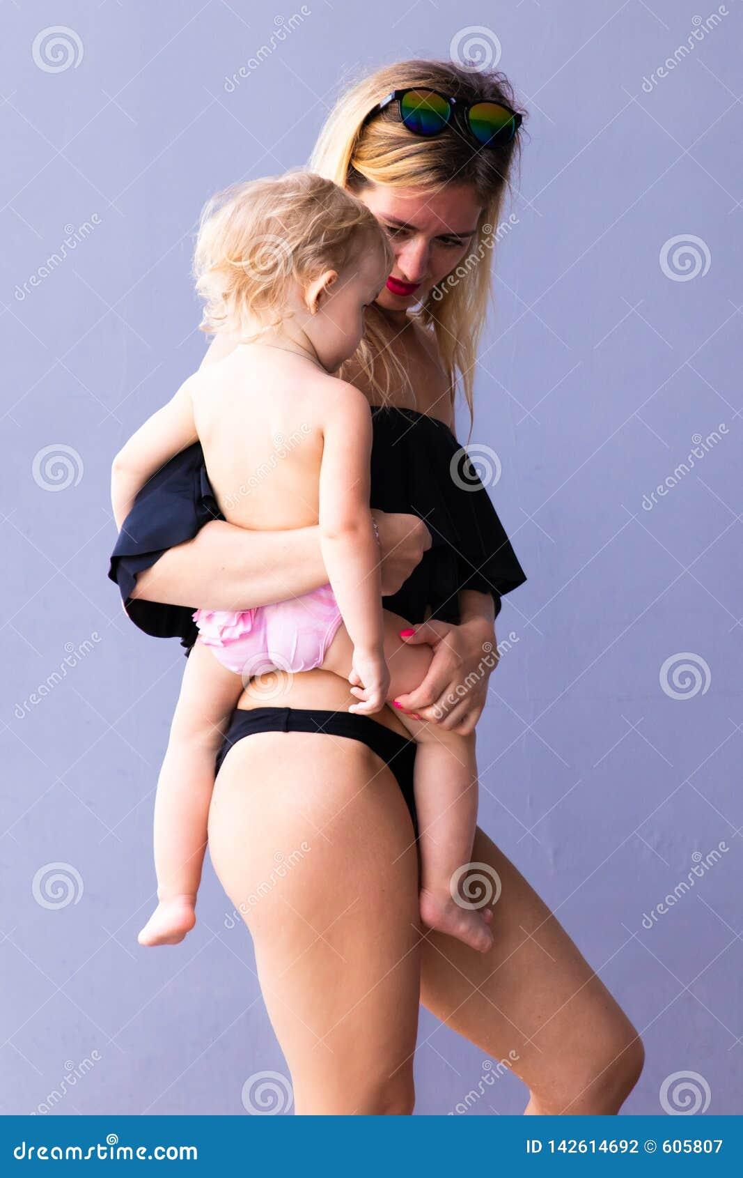 有一个婴孩的女性她的胳膊皱眉的和笑的反对蓝色背景