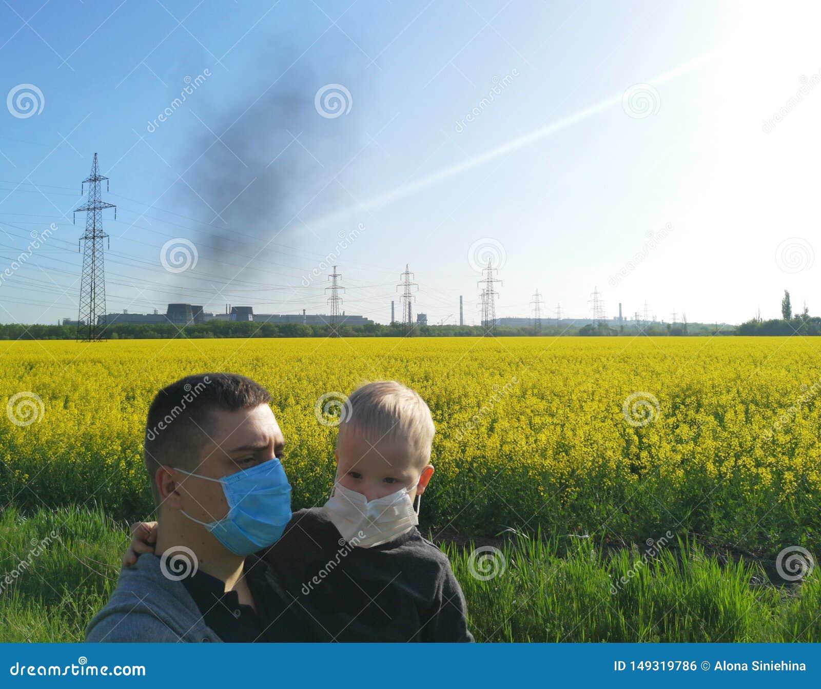 有一个孩子的一个人在他的在医疗面具的手上在植物的背景 环境污染,生态的概念