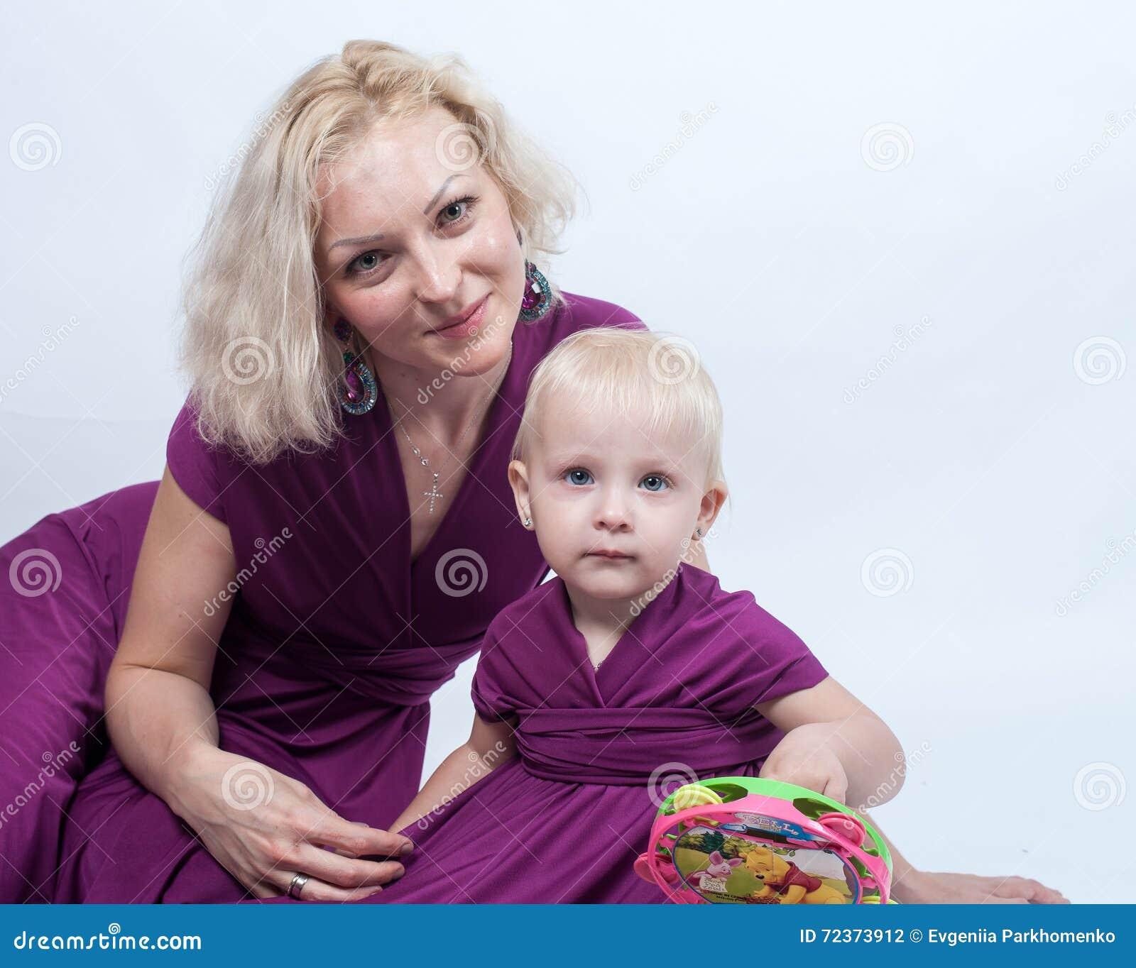 有一个小女儿的白肤金发的妇女匹配的穿戴