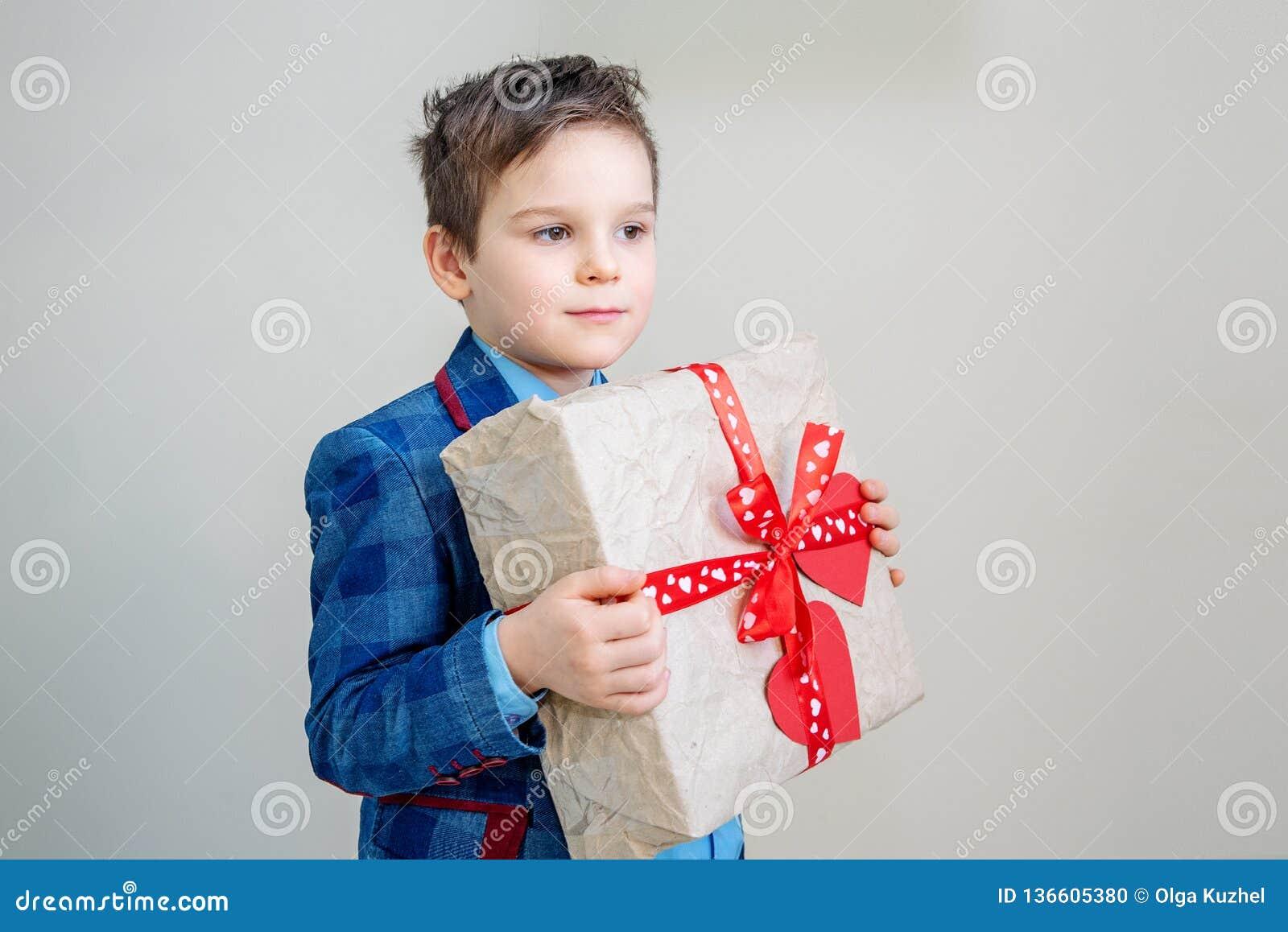 有一个礼物盒的可爱的男孩在轻的背景
