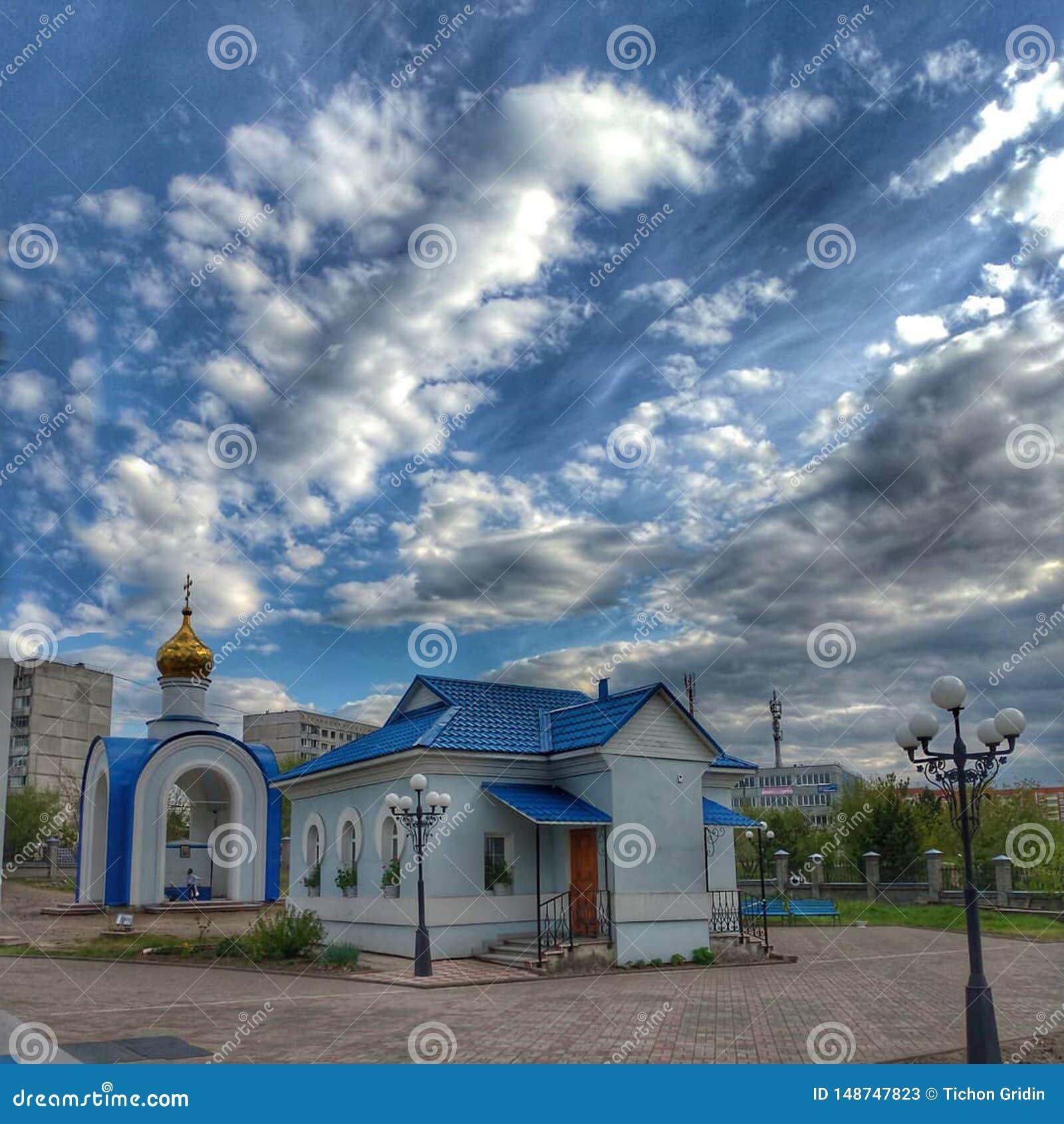 有一个蓝色屋顶的一个小屋,与Golden Dome的一个大厦和与白色云彩的一明亮的天空蔚蓝,索斯诺沃博尔斯克,克拉斯诺亚尔斯克r