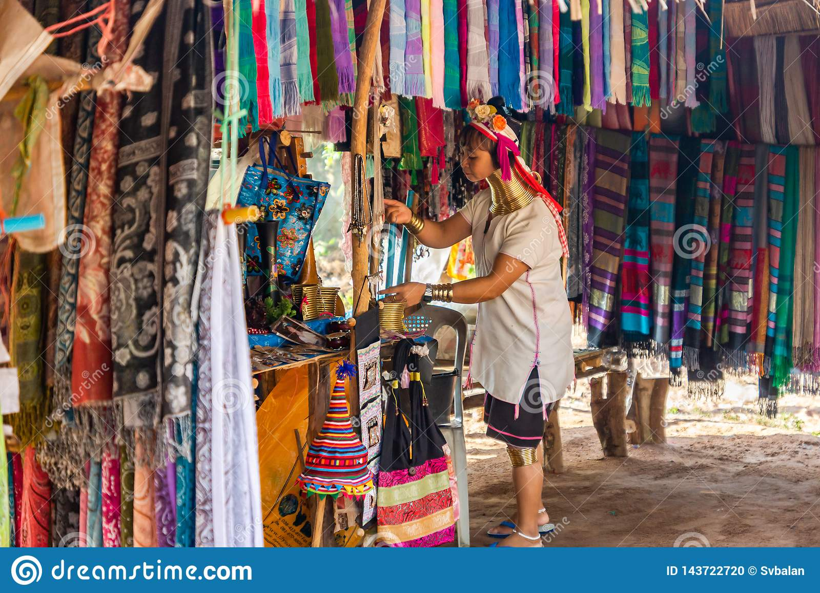 有一个长的脖子和圆环的一名妇女在她一个柜台为丝绸围巾做准备销售