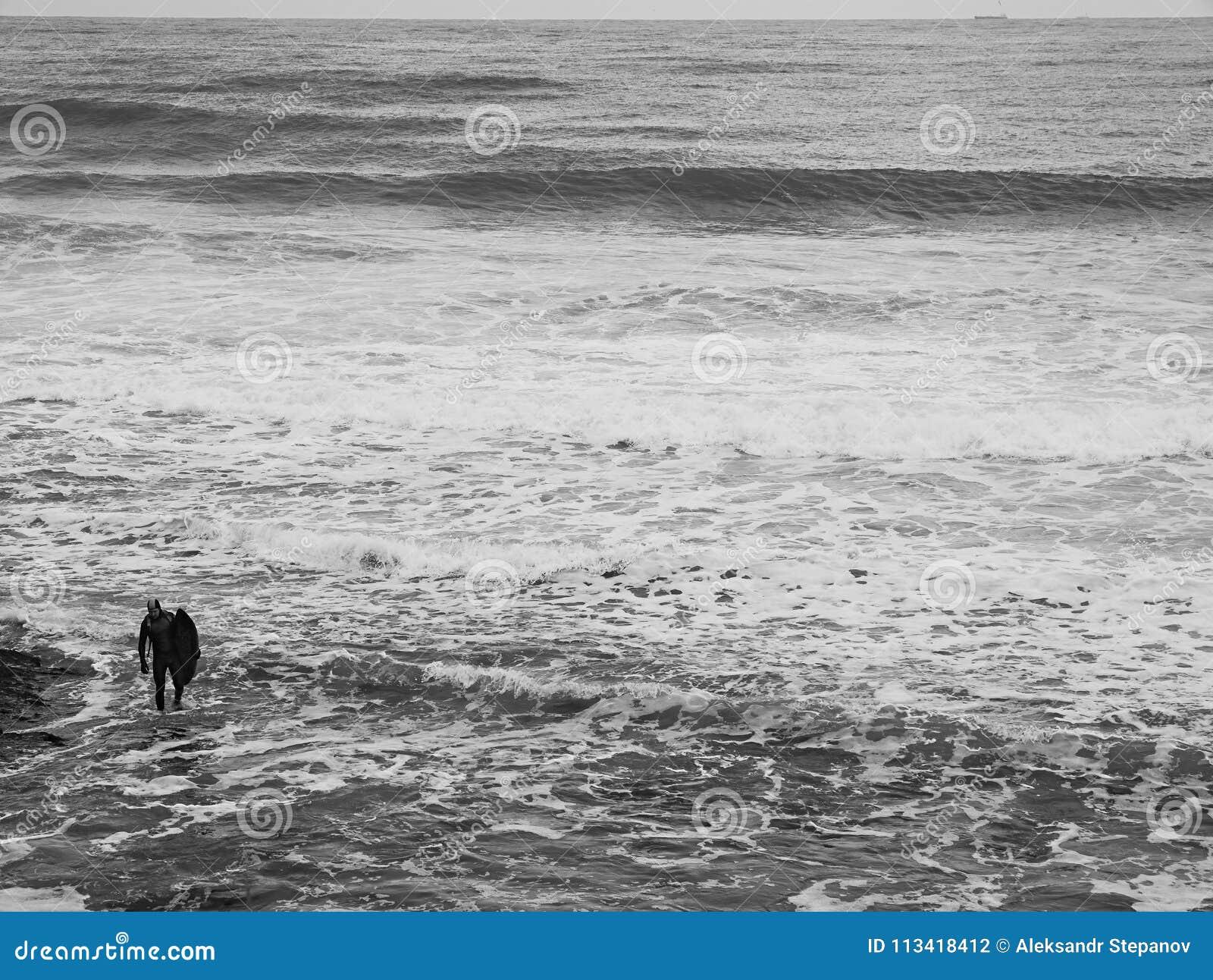 有一个风帆冲浪委员会的一个人以波浪为背景和海起泡沫