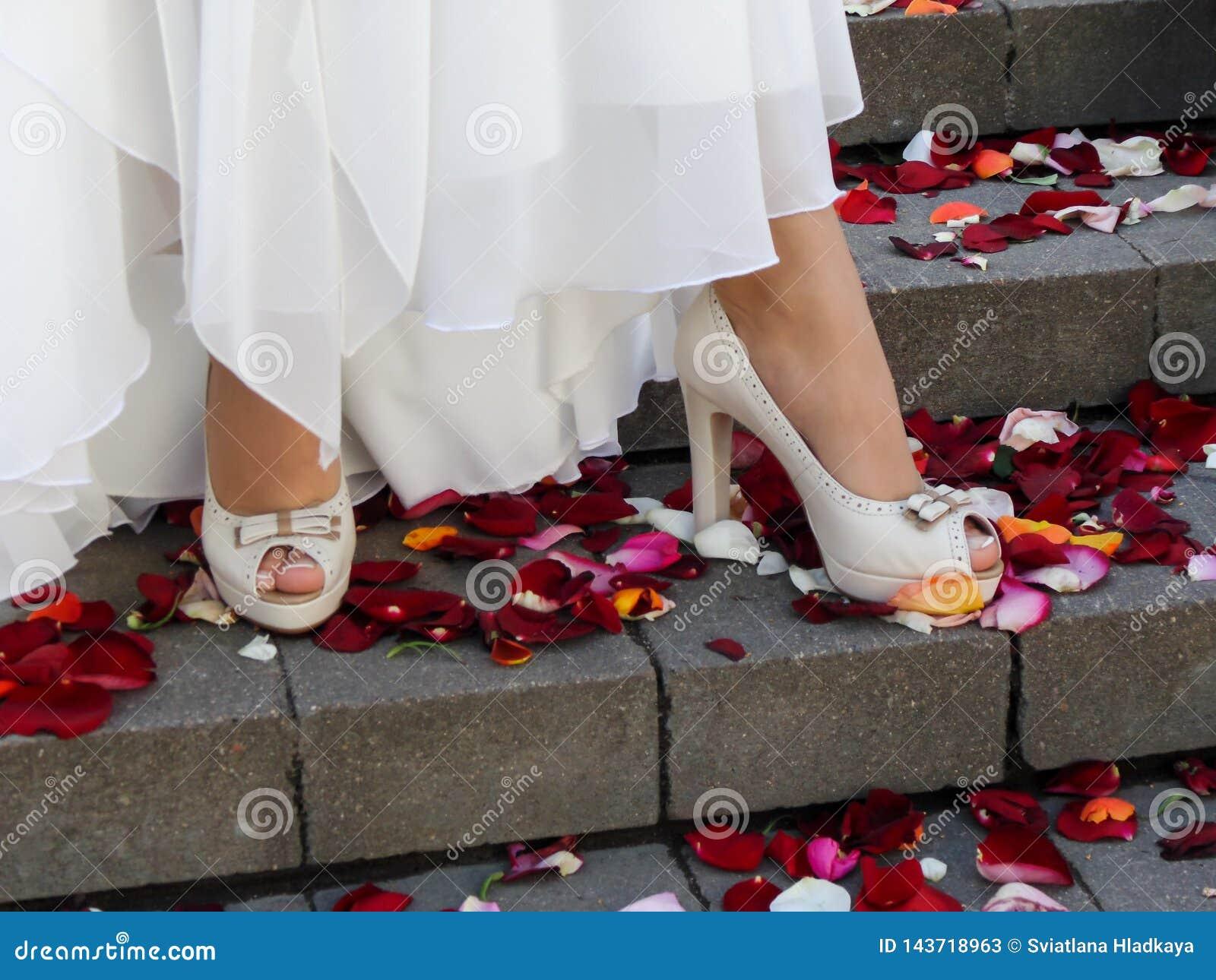 有一修脚的美好的穿着考究的女性腿在有脚跟的米黄开放鞋子在台阶的步站立