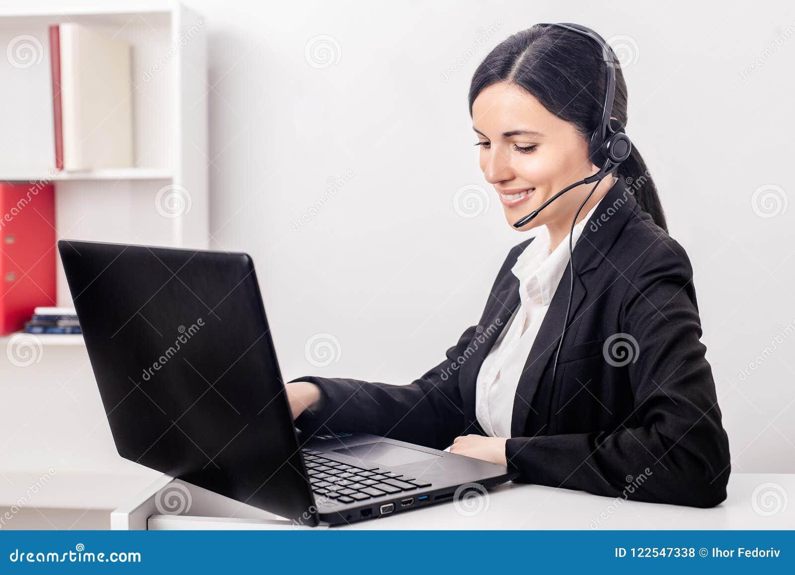 有一台膝上型计算机的女孩在办公室谈话在耳机