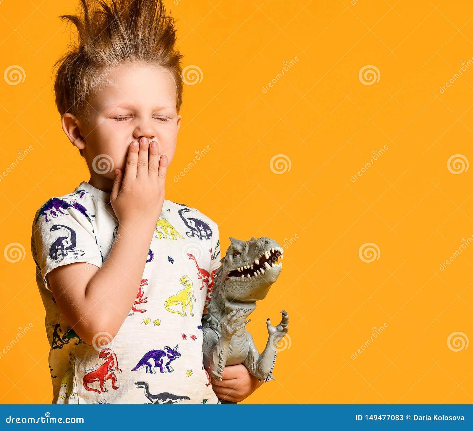 有一根滑稽,被弄乱的头发的小男孩拿着玩具塑料恐龙作为画象