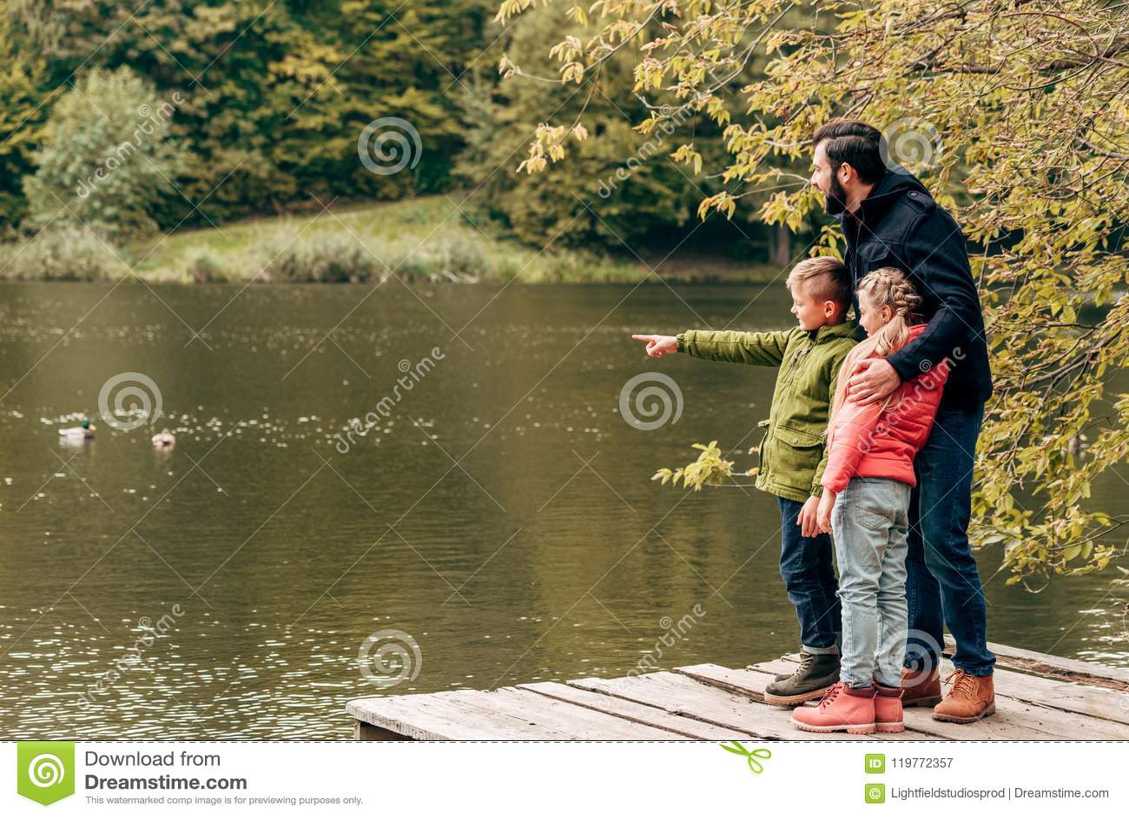 有一起站立和看湖的可爱的小孩的愉快的父亲