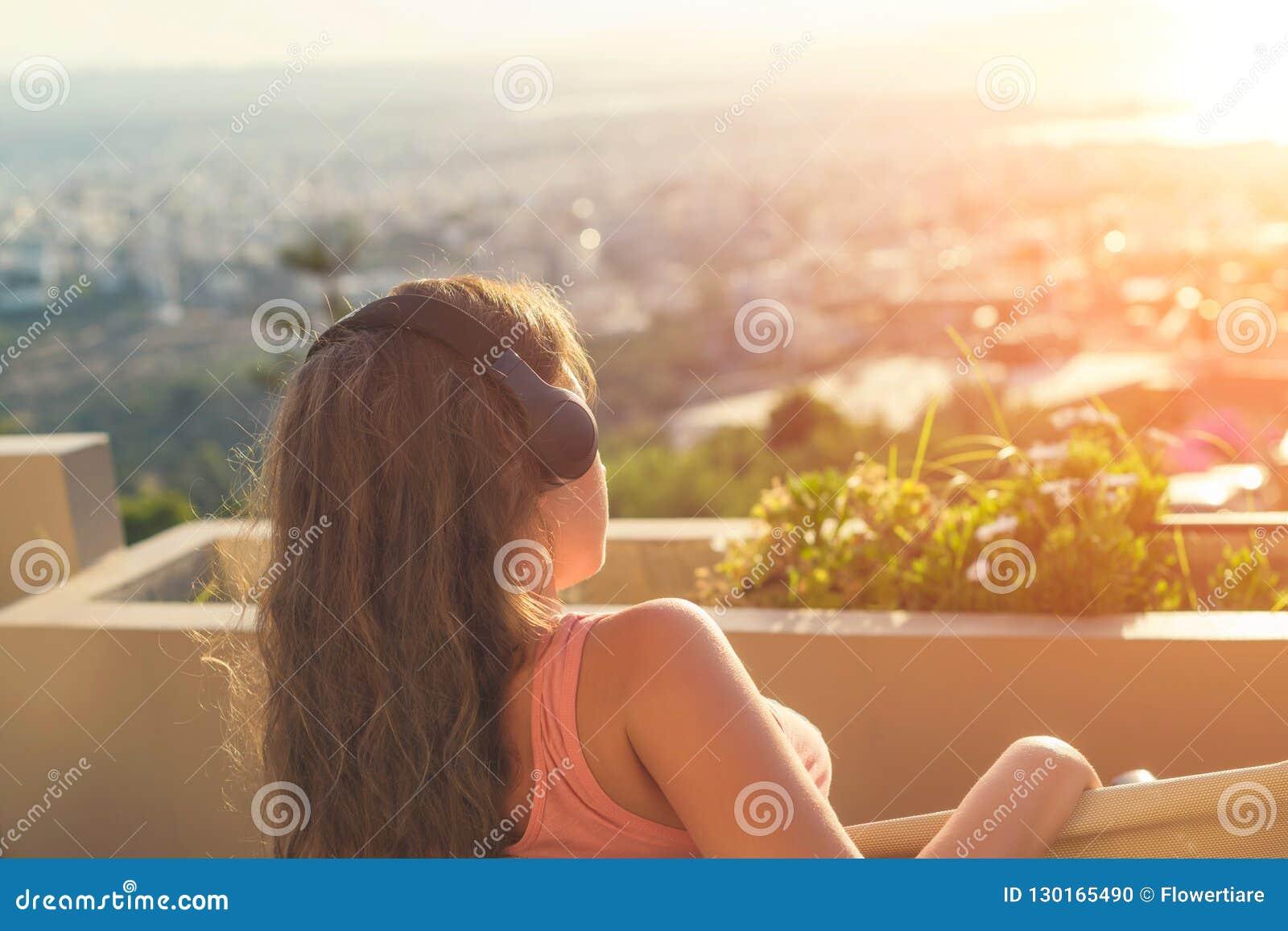 有一长发的女孩在椅子的耳机在阳台听到在日落背景的音乐的