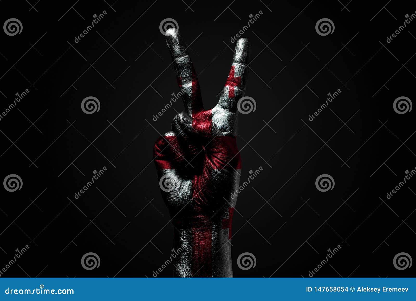 有一面拉长的乔治亚旗子的一只手显示和平标志、和平的标志,友谊、问候和和平在黑暗