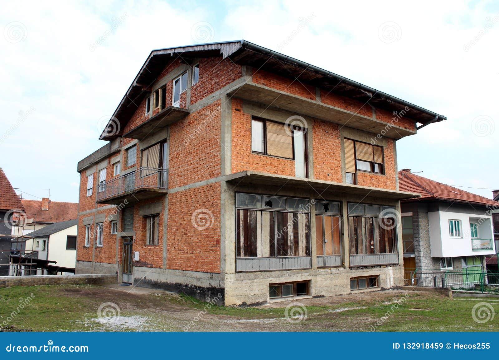 有上的前窗和门的未完成的红砖郊区家庭房子围拢与草和其他房子