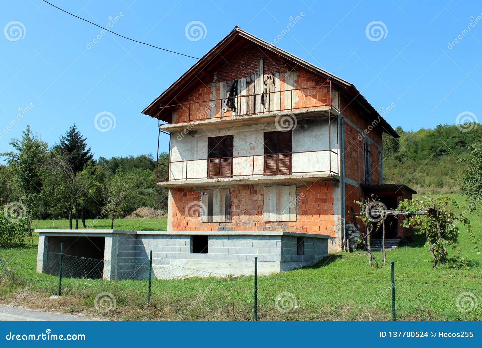 有上的窗口的高未完成的被放弃的红砖家庭郊区与树和清楚的天空蔚蓝的房子和门
