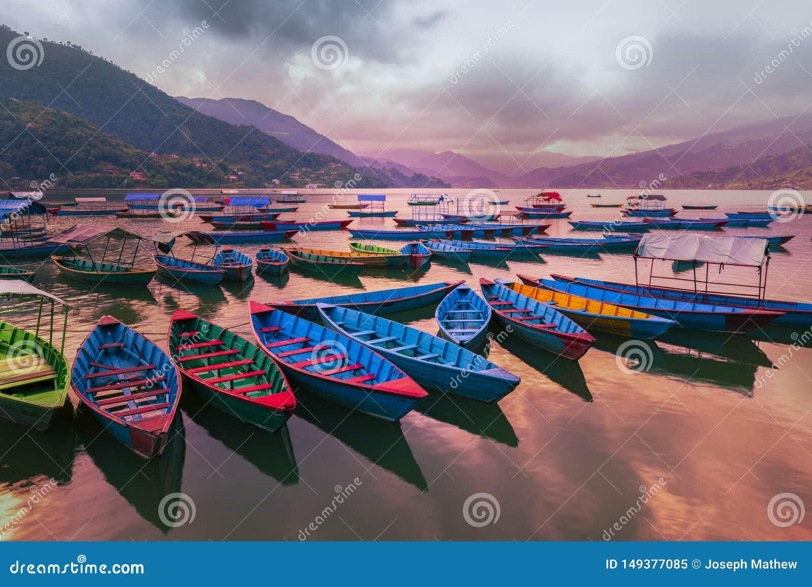 有不同颜色的小船,天空蔚蓝反射在水中 从Phewa湖的看法