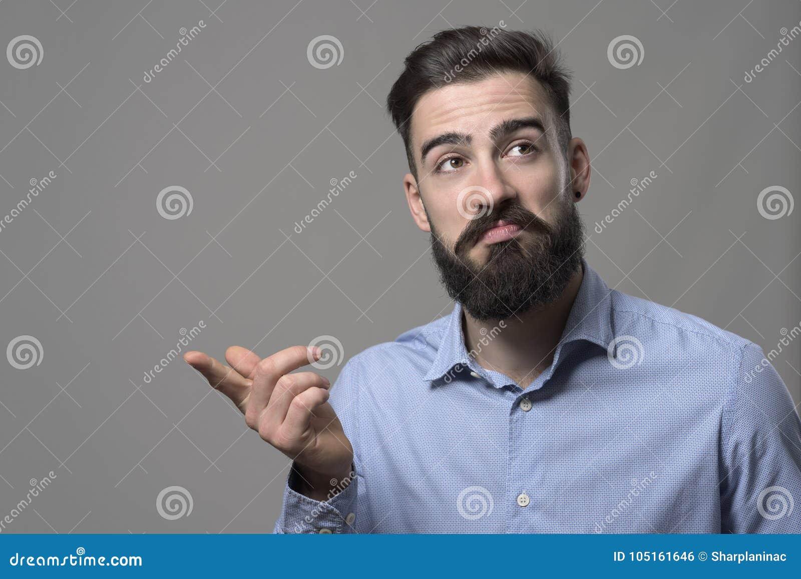有不坏面部认同表示的年轻有胡子的聪明的偶然商人把手指指向的copyspace