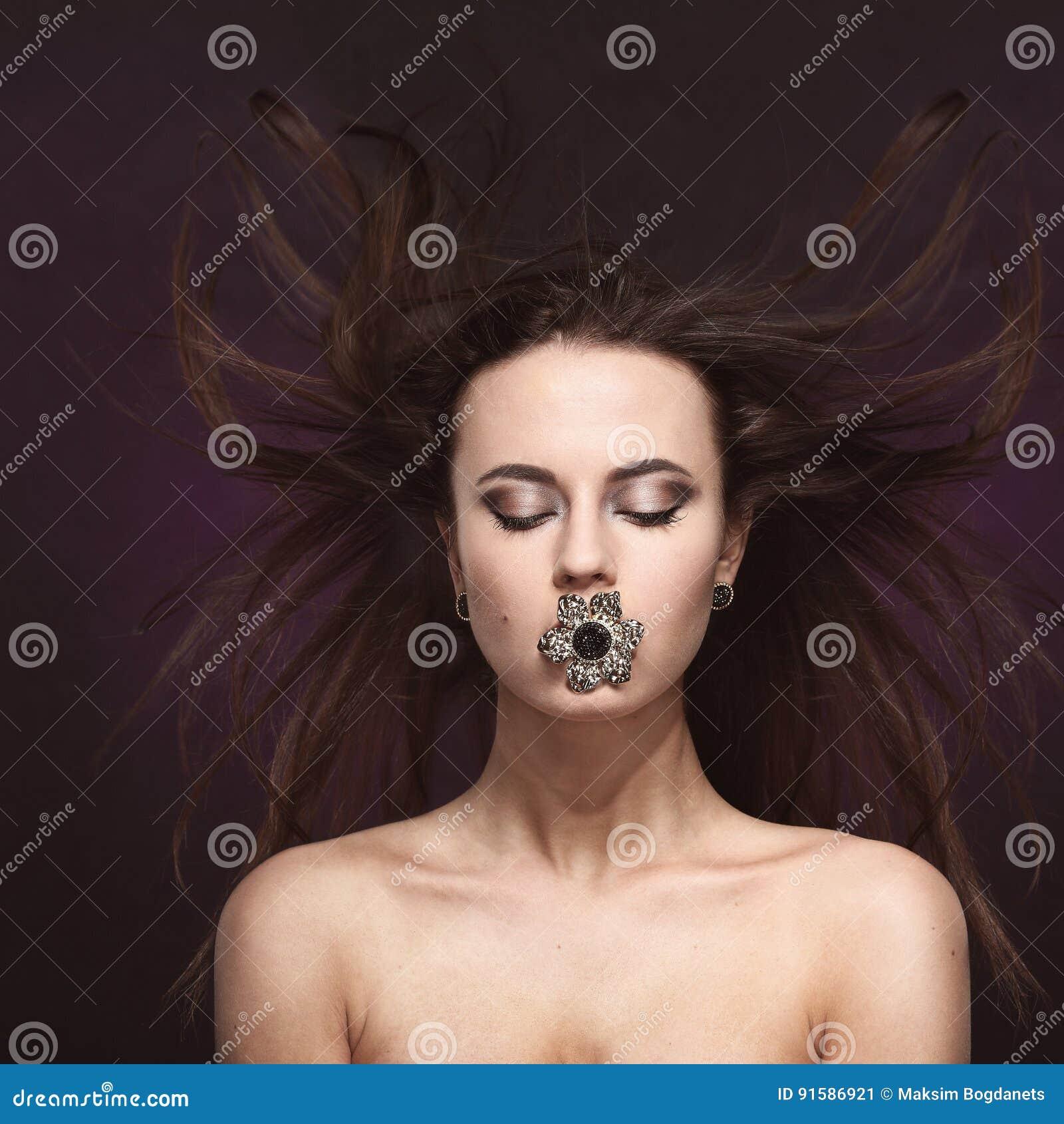 有专业显示大圆环的构成和发型的美丽的深色的妇女在嘴和耳环 登广告者做广告 飞行灰色头发夫人年轻人的有吸引力的背景梳子