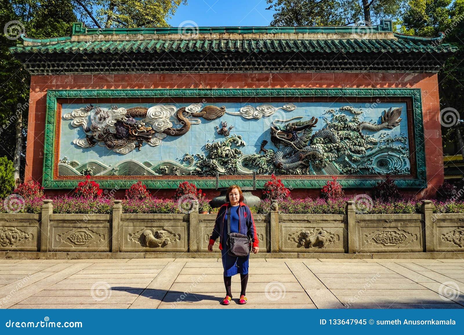 有两中国龙的亚裔资深妇女在'祖先寺庙的'蓝色墙壁上