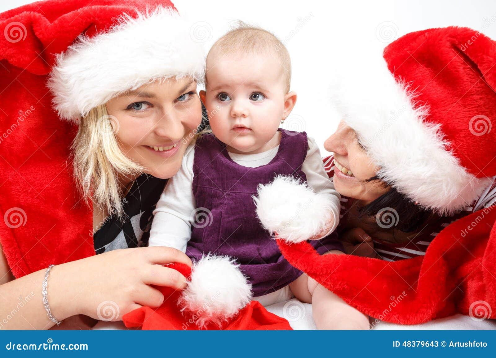 有两名妇女的微笑的婴儿婴孩有圣诞老人帽子的