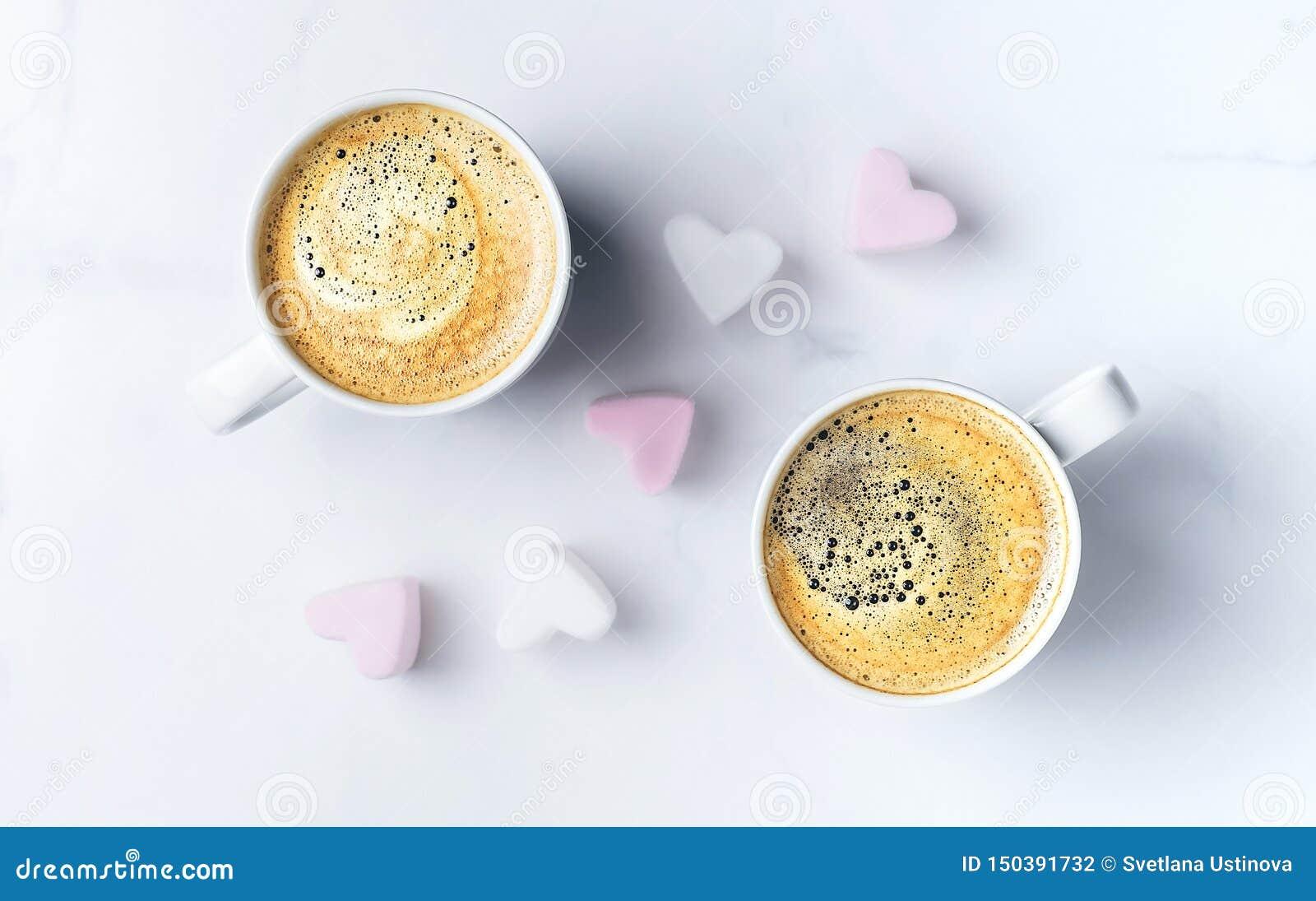 有两杯咖啡的浪漫桌面和桃红色心形的蛋白软糖 r