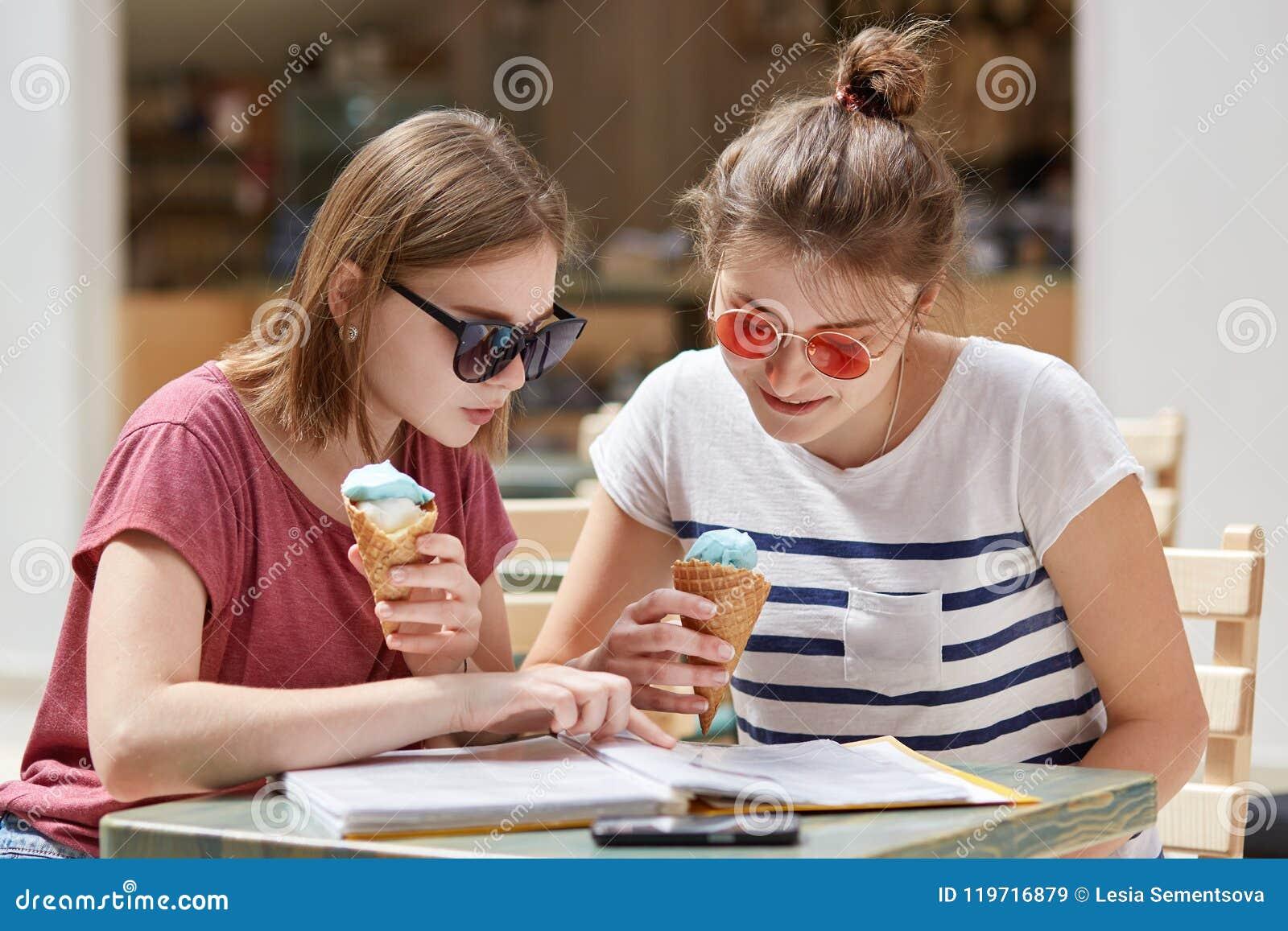 有严肃的表示的两个最佳的女性伴侣,被聚焦在菜单,选择怎样在自助食堂吃,享用冰淇凌, dres