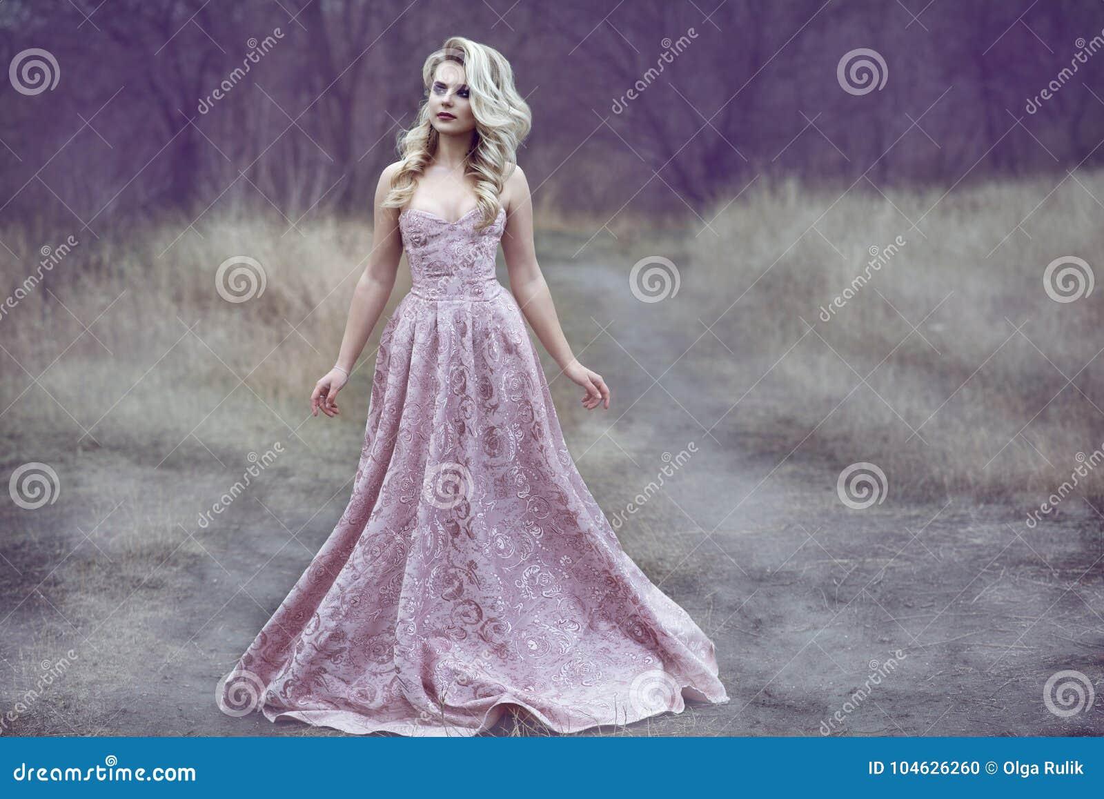 有丰富的发型的华美的白肤金发的夫人在长的锦礼服走沿狭窄的道路的在森林