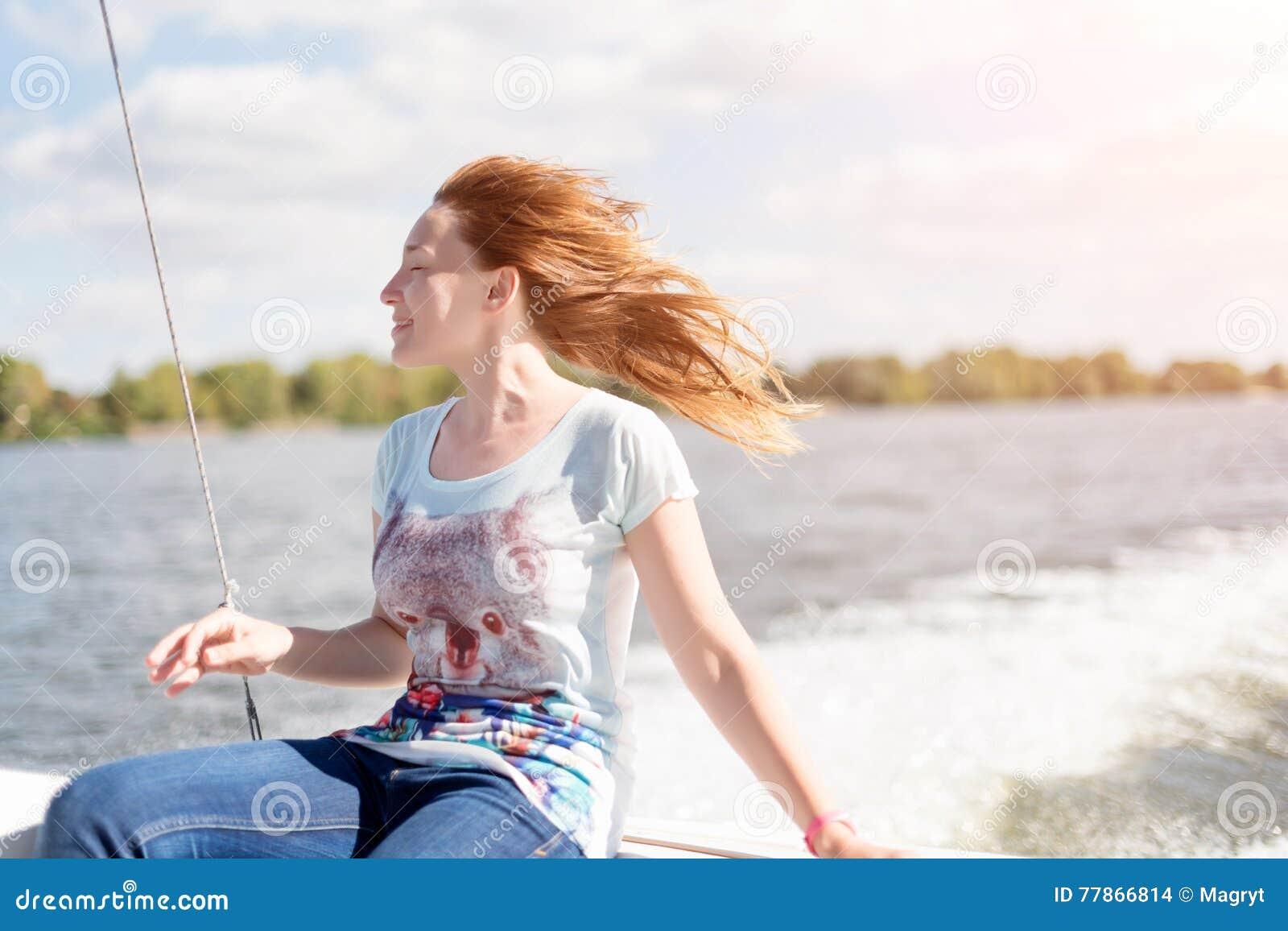 有乐趣的闭合的眼睛的轻松的少妇坐风船,享受温和的阳光、海或者河巡航,暑假