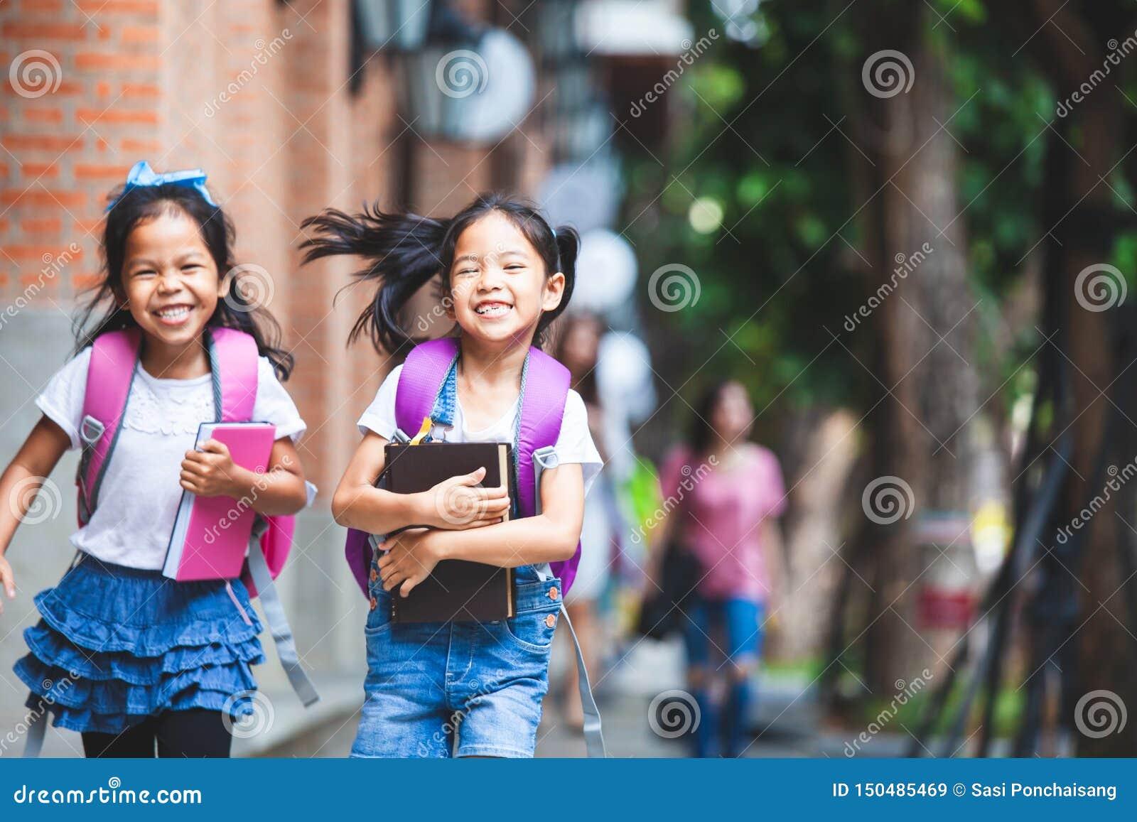 有书包一起藏品书和步行的两个逗人喜爱的亚裔儿童女孩在学校
