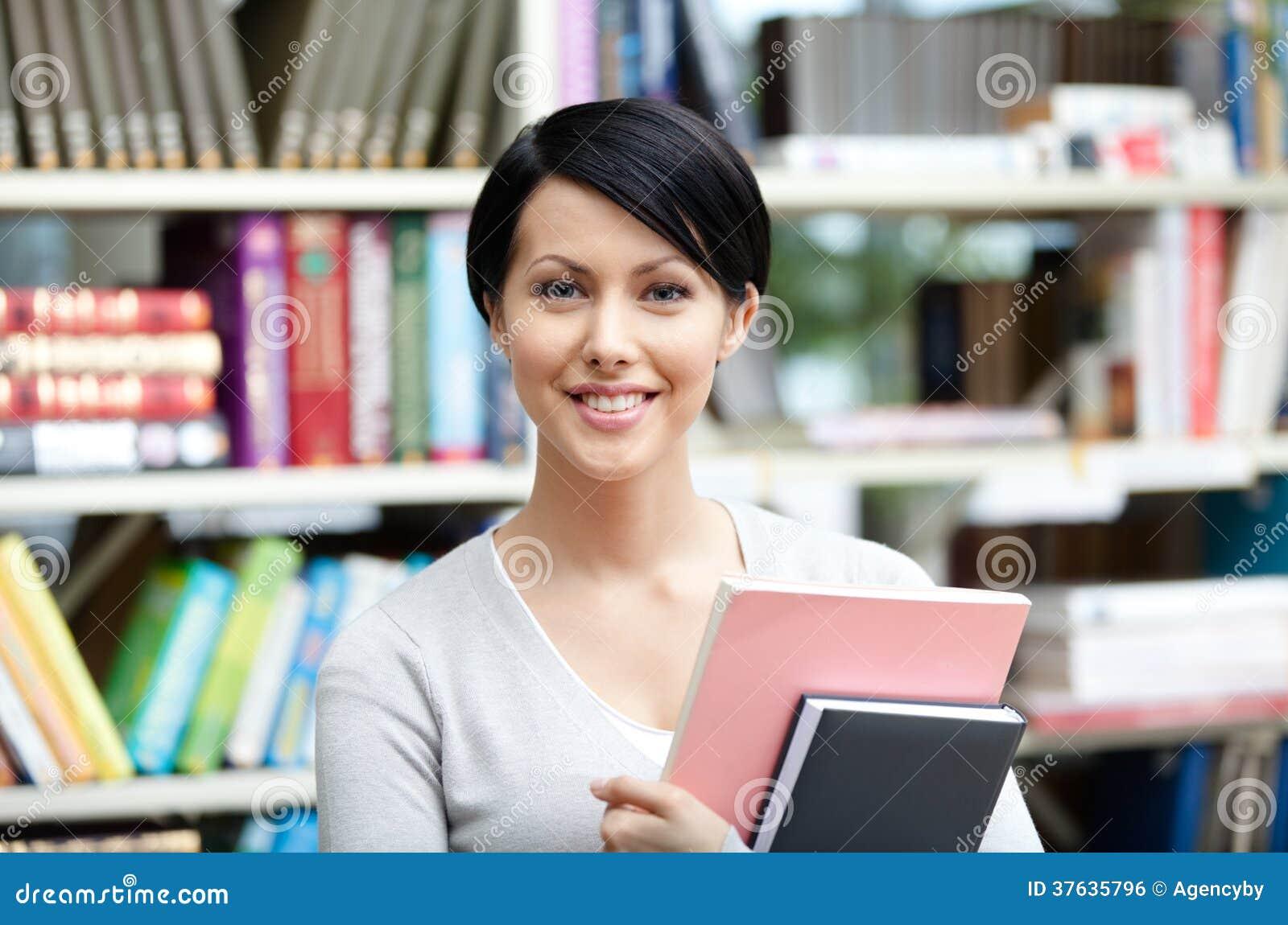 有书的兴高采烈的学生在图书馆