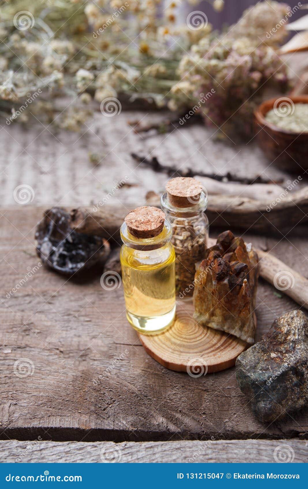 有乳化液、石头和木细节的瓶 隐密,神秘,占卜和wicca概念 神秘,老药商