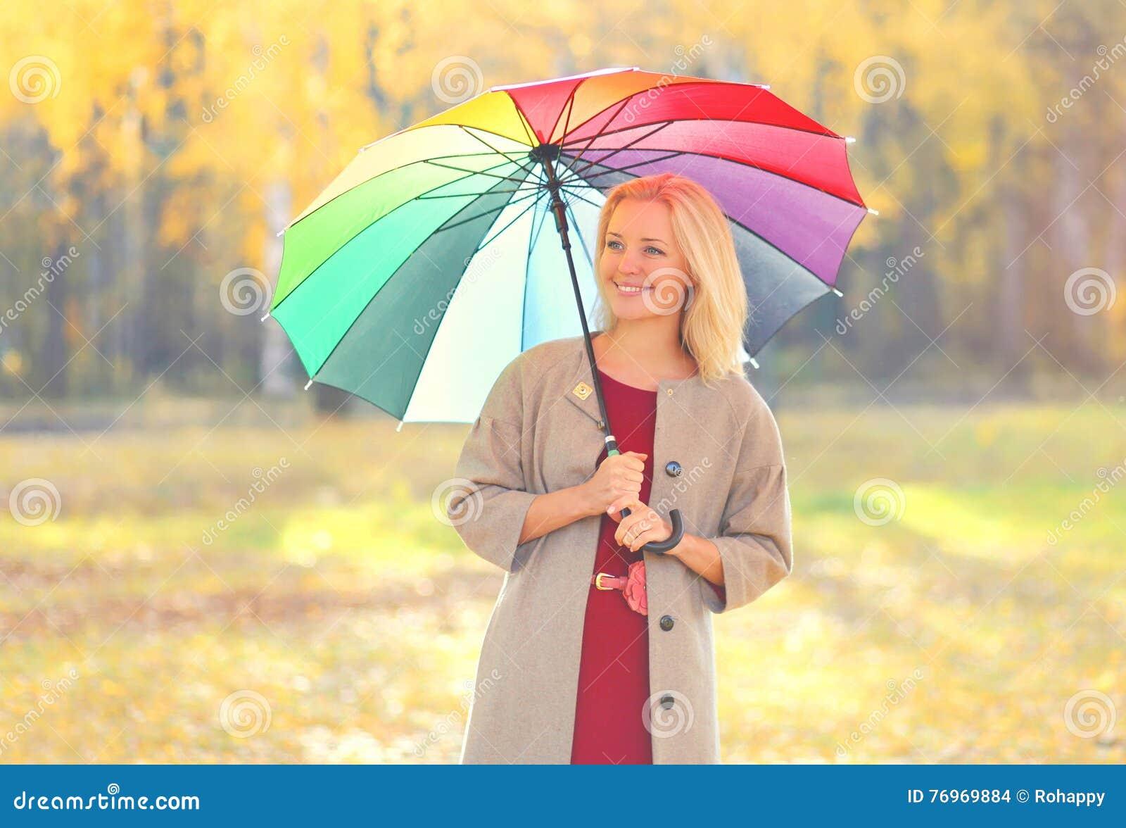 有五颜六色的伞的画象美丽的微笑的妇女在温暖的晴朗的秋天天