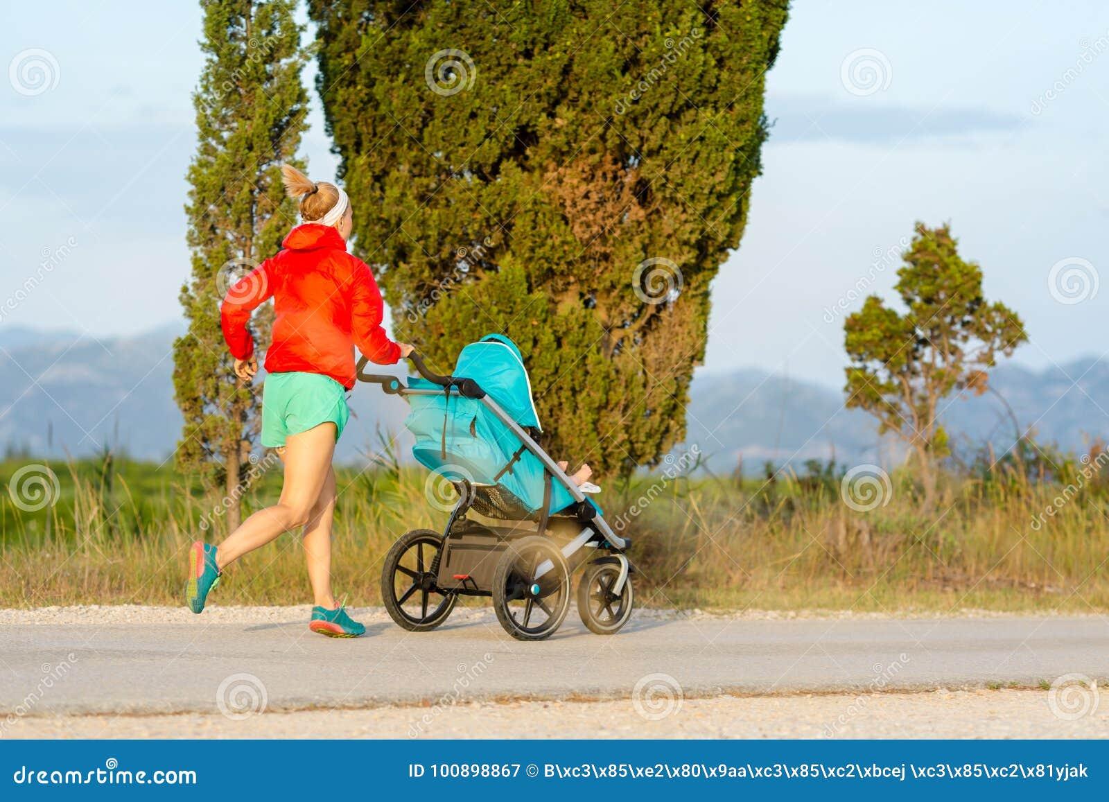 有享受母性的婴儿推车的连续母亲在日落登陆