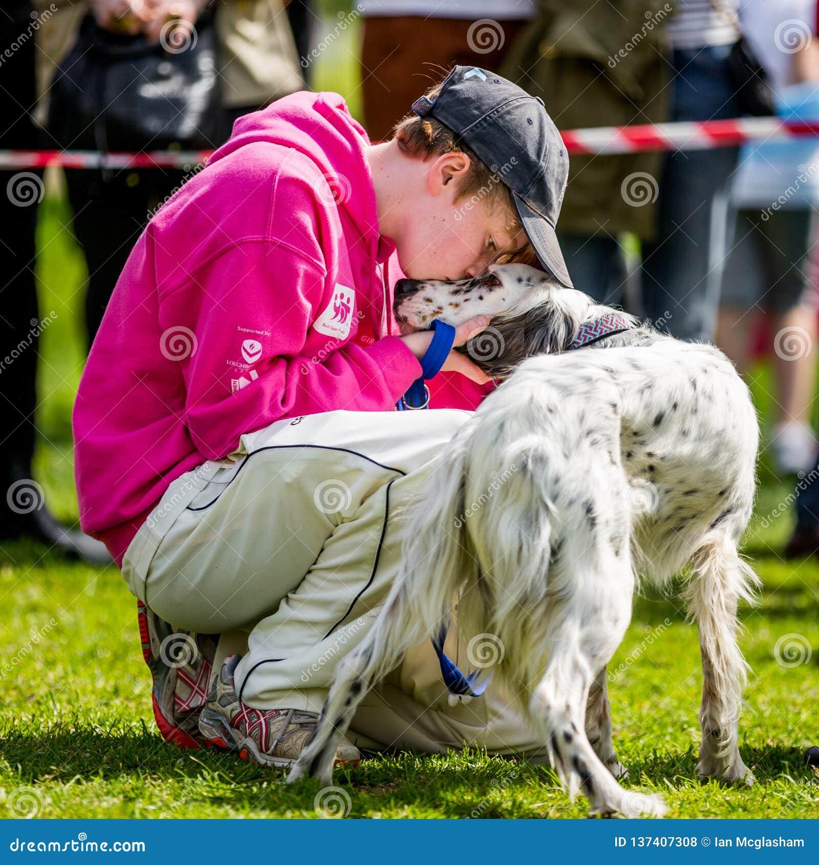 有亲吻他的巨鼻的狗的一个年轻男孩在汉普斯德希斯狗展示