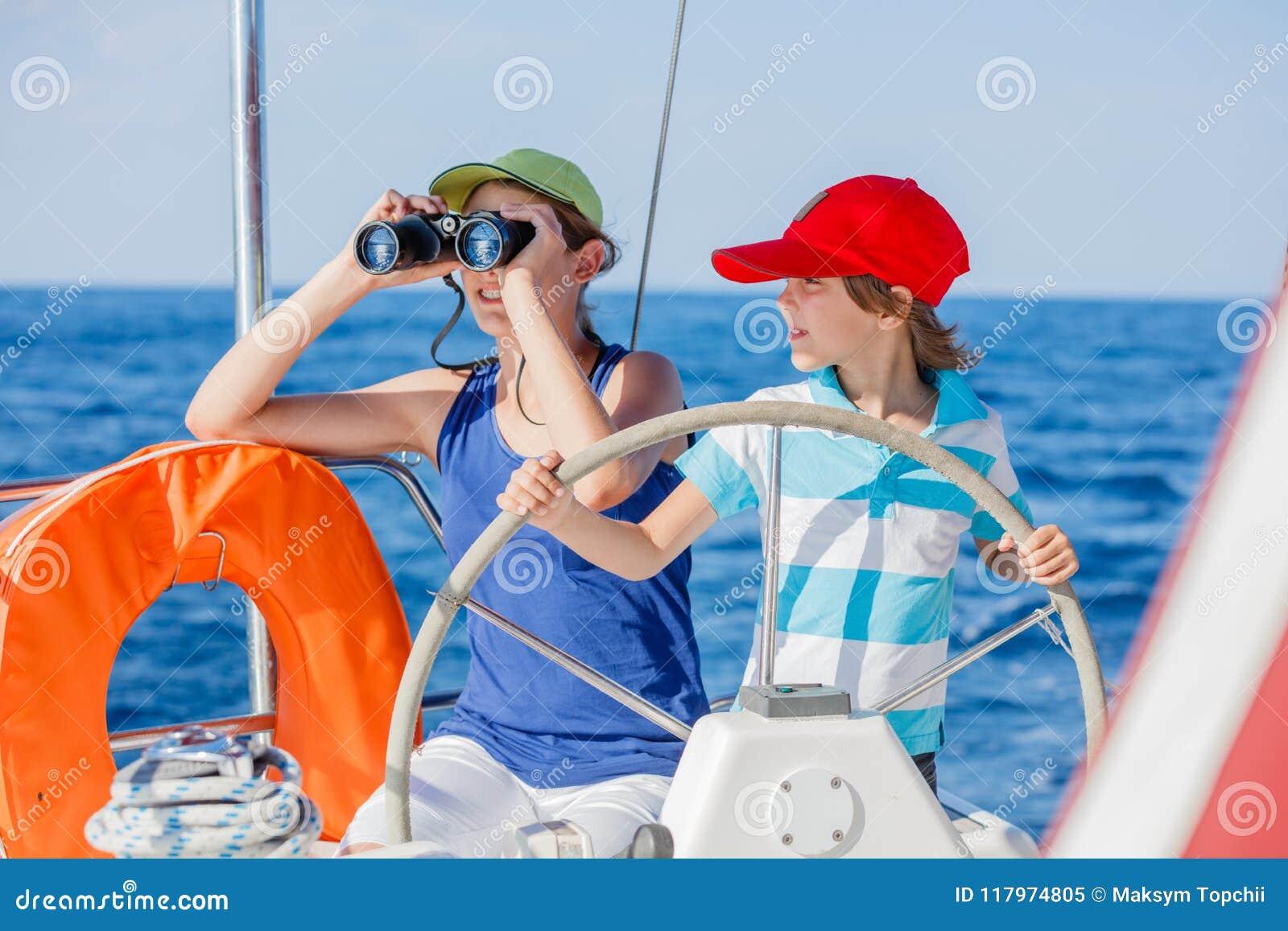 有他的姐妹的男孩上尉在船上在夏天巡航的航行游艇 旅行冒险,乘快艇与家庭的孩子