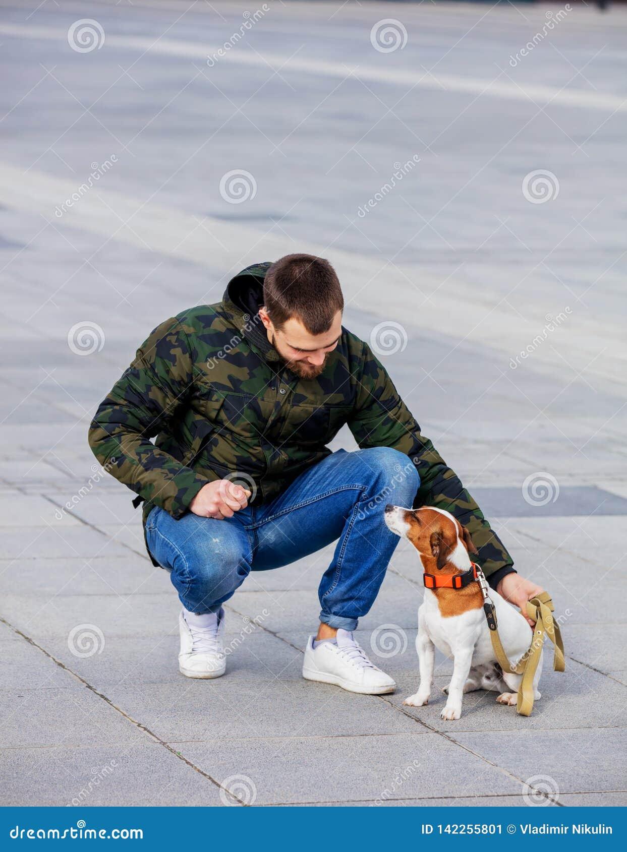 有他的狗的人,杰克罗素狗,在城市街道上