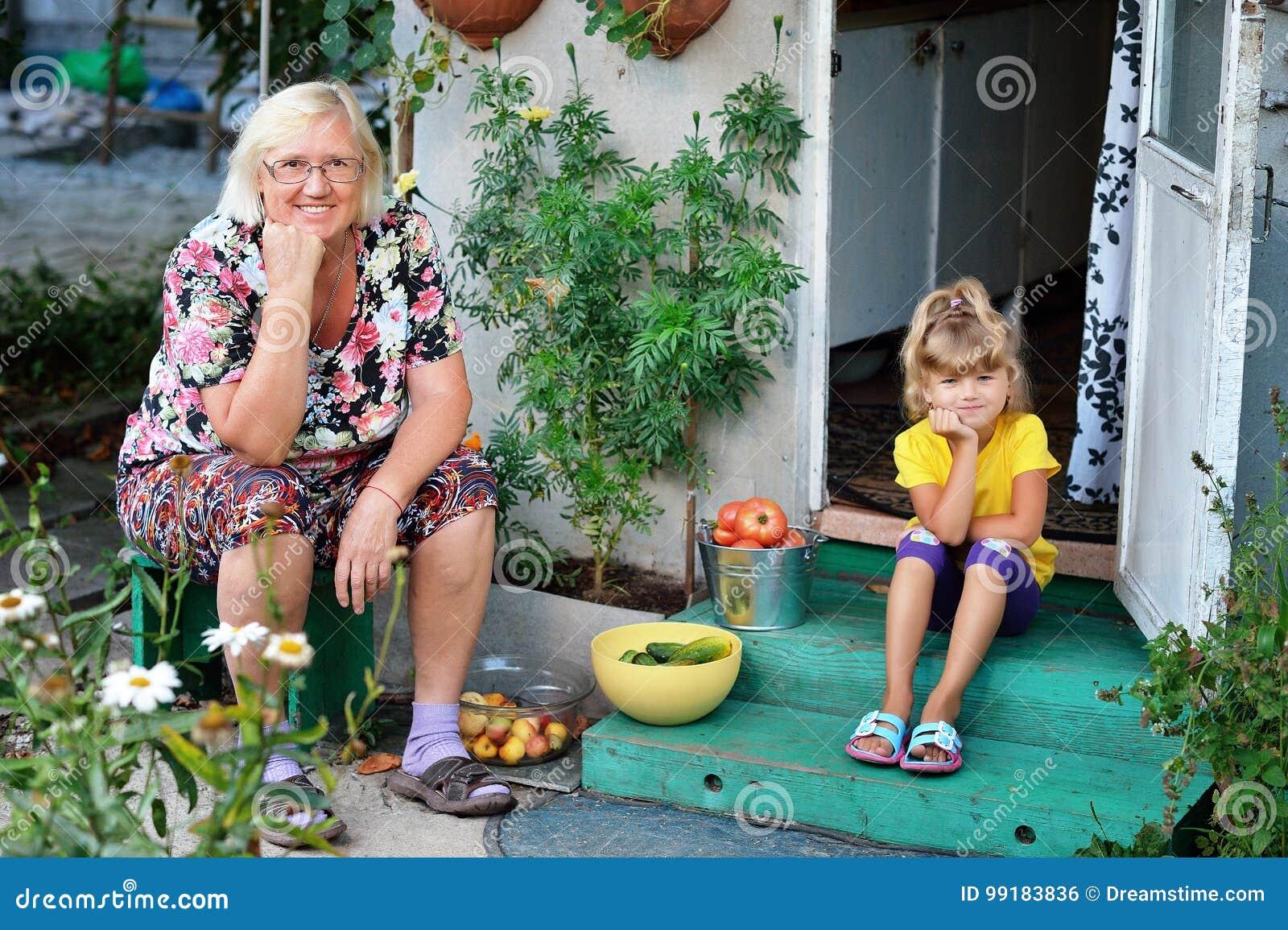 有他的祖母的孙女收集了蕃茄庄稼,